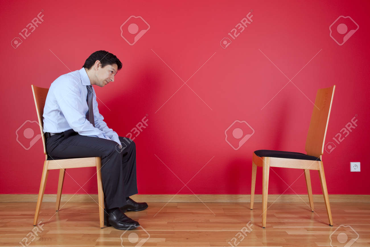 Businessman sited next to a red wall Stock Photo - 16389267