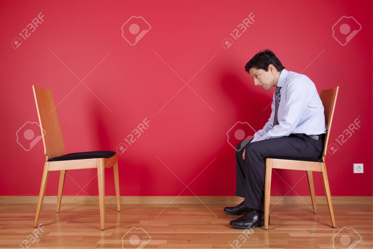 Businessman sited next to a red wall Stock Photo - 16389167
