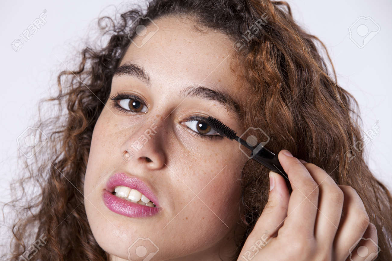 Beautiful young woman applying the eyeliner Stock Photo - 16389190