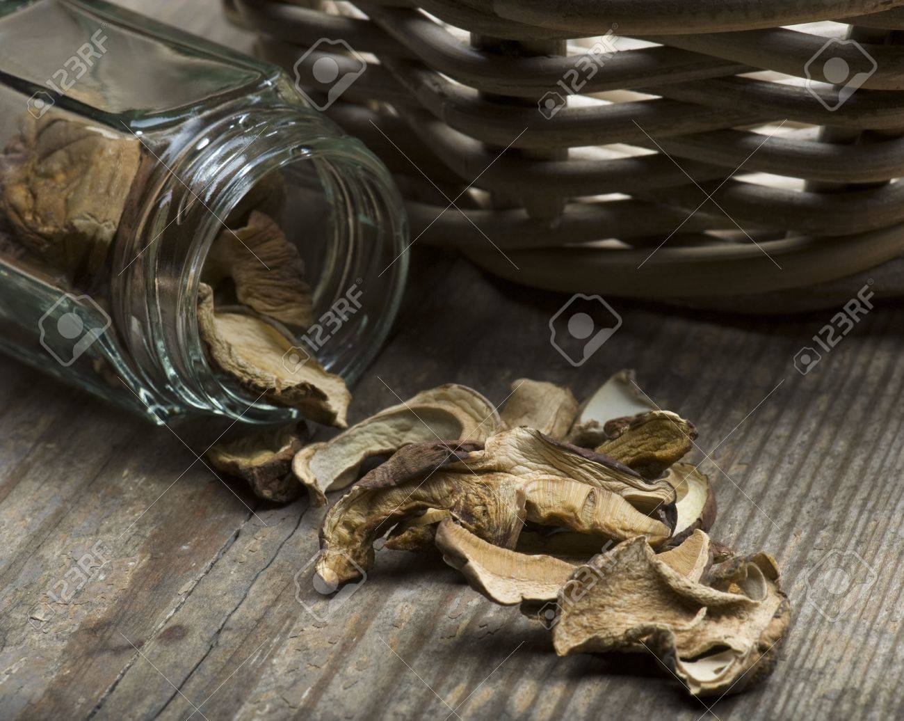 Dried Porcini Mushrooms Spilling Out Of A Jar Onto A Rustic Table, With A basket In The Background - 6951576