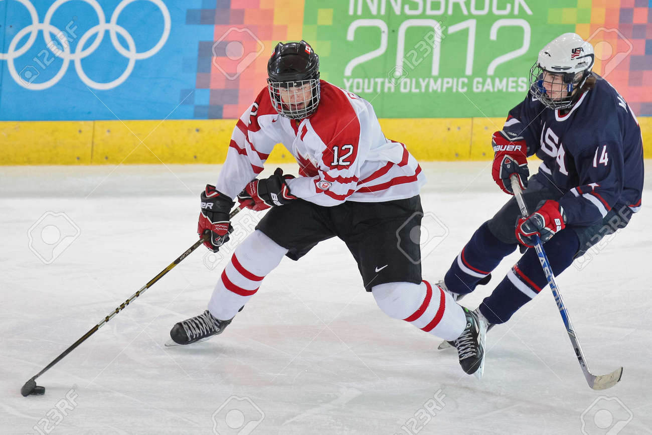 INNSBRUCK, AUSTRIA - JANUARY 21 Eric Cornel (Canada) and Ryan Macinnis (USA) fight for the puck as Canada beats the USA 7:5 in the men's ice hockey tournament and wins the bronze medal on January 21, 2012 in Innsbruck, Austria. Stock Photo - 12160147