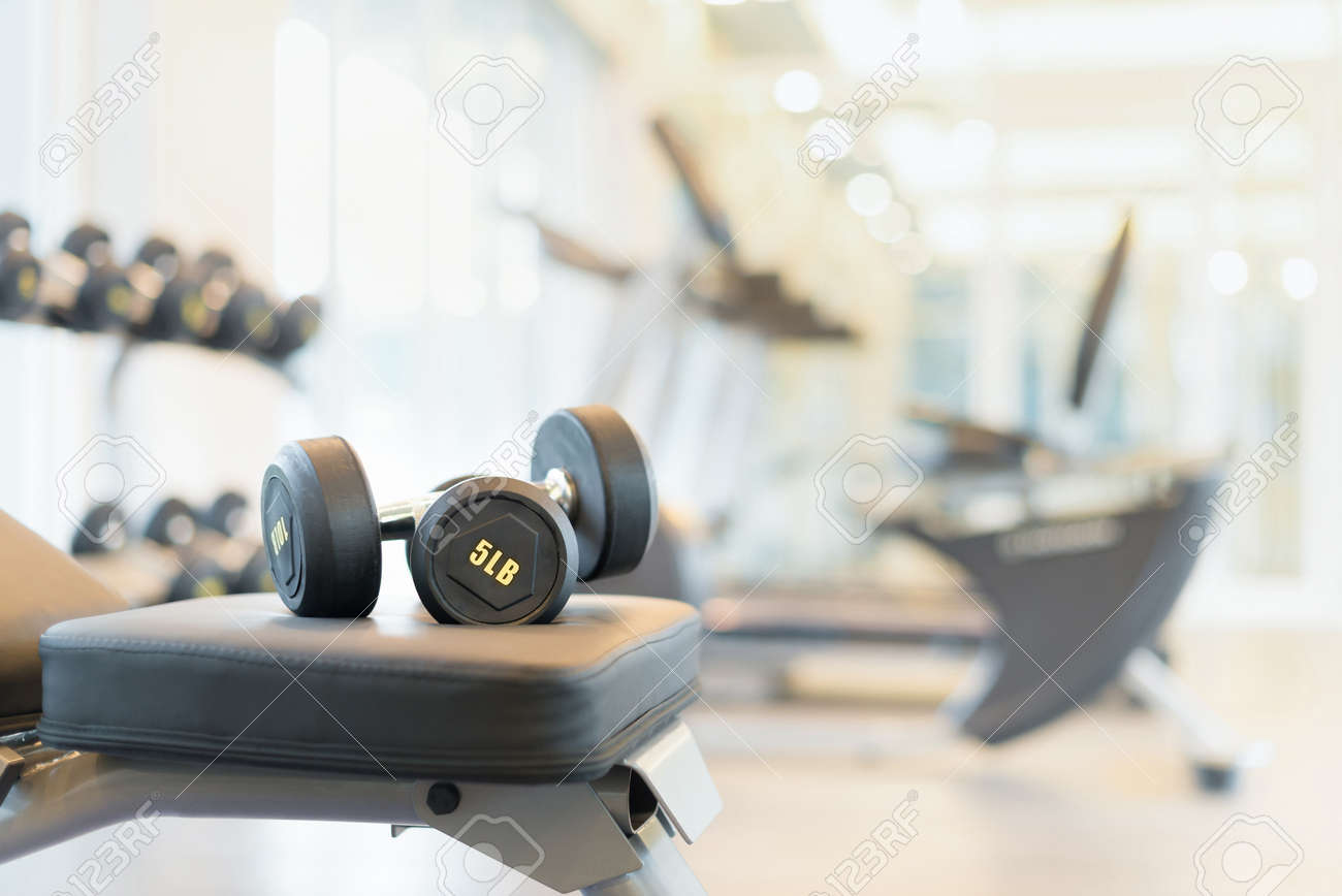 Two dumbbells on the exercise bench. Gym equipment. - 54635511