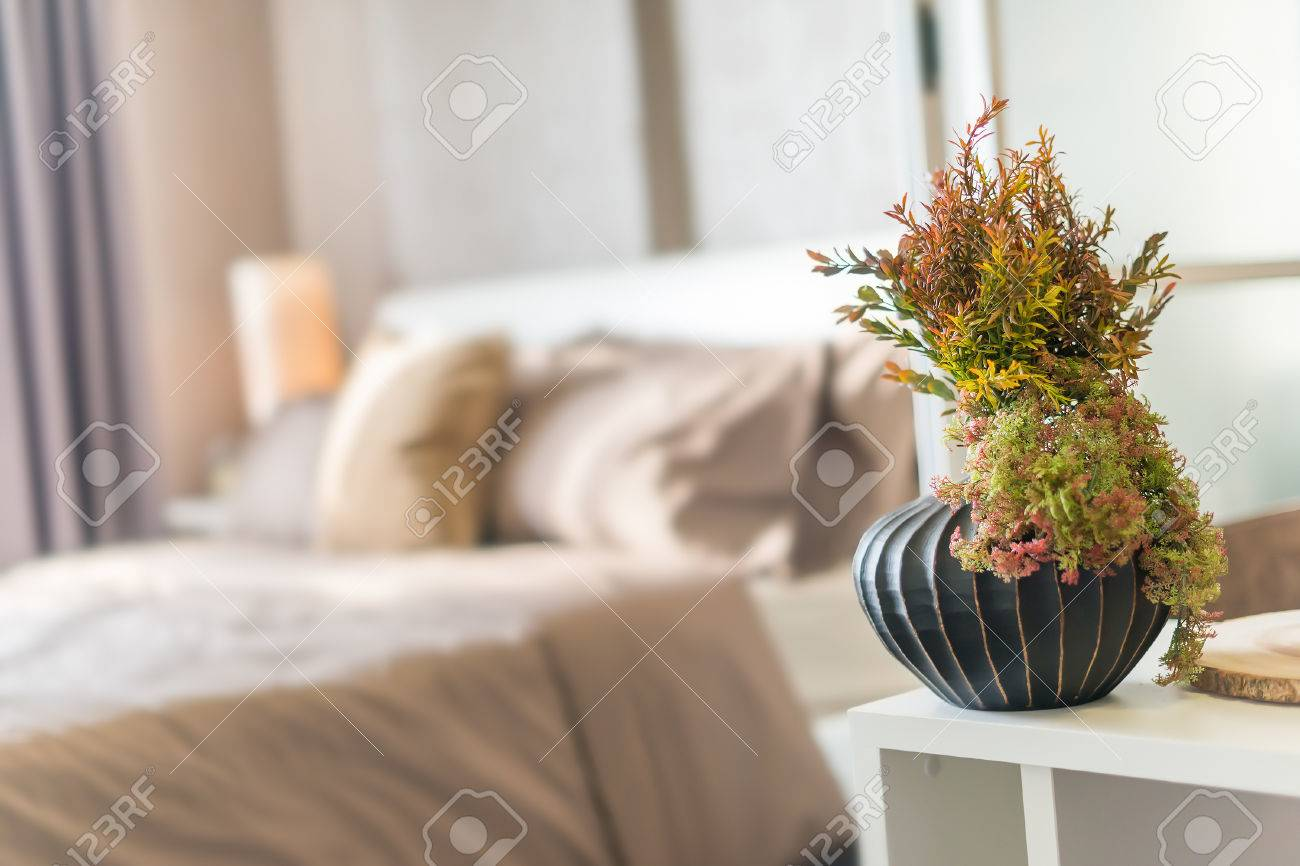 House decoration, plastic plants in vase on white desk, bedroom