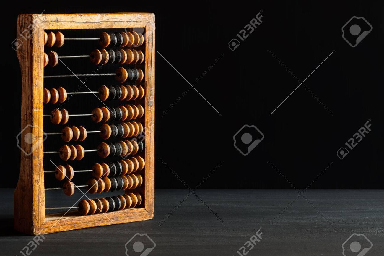 Vieux boulier décimal vintage rayé en bois sur un bureau noir de