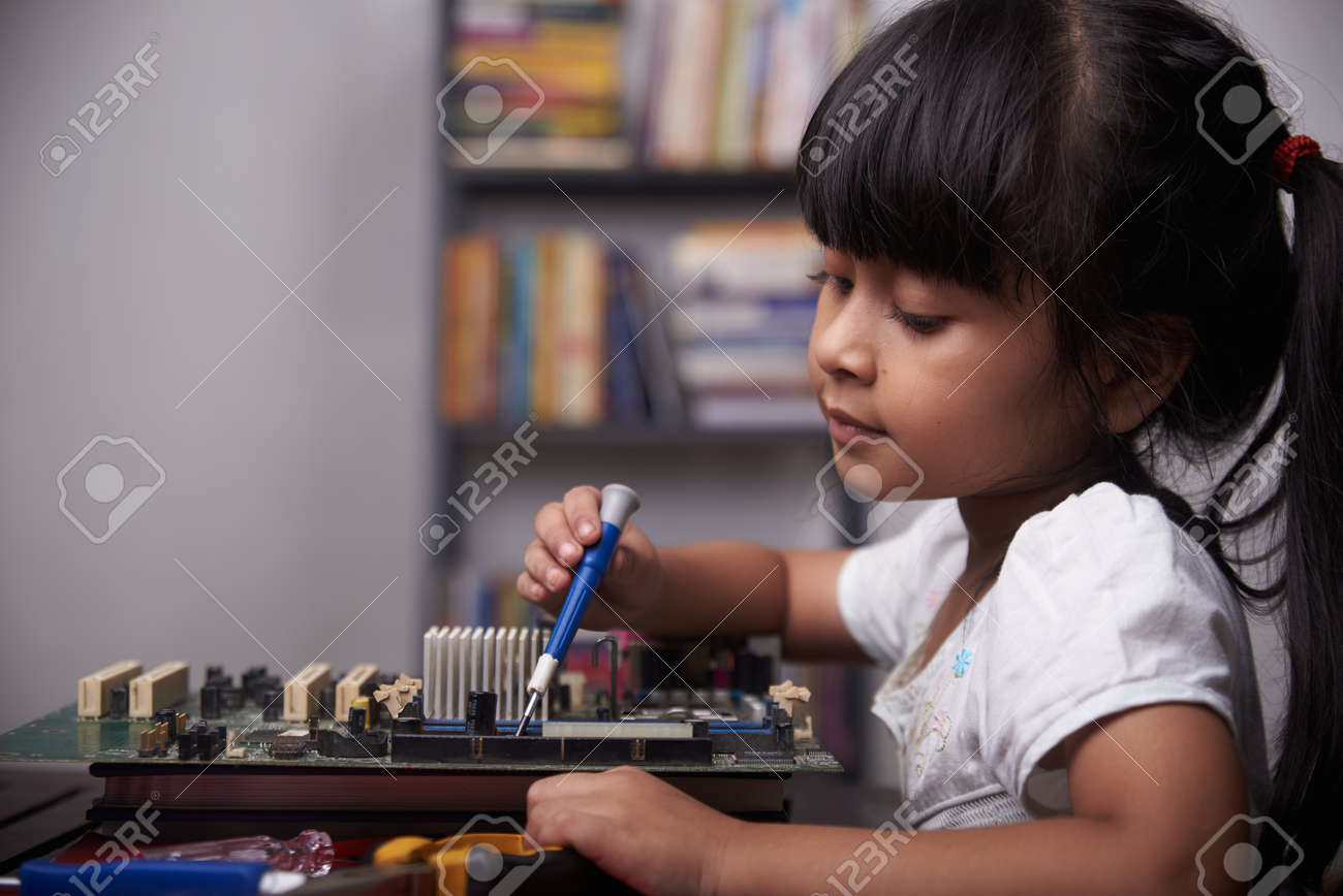 Little cute girl playing with broken computer part, kids creativity study at home during pandemic - 168492745
