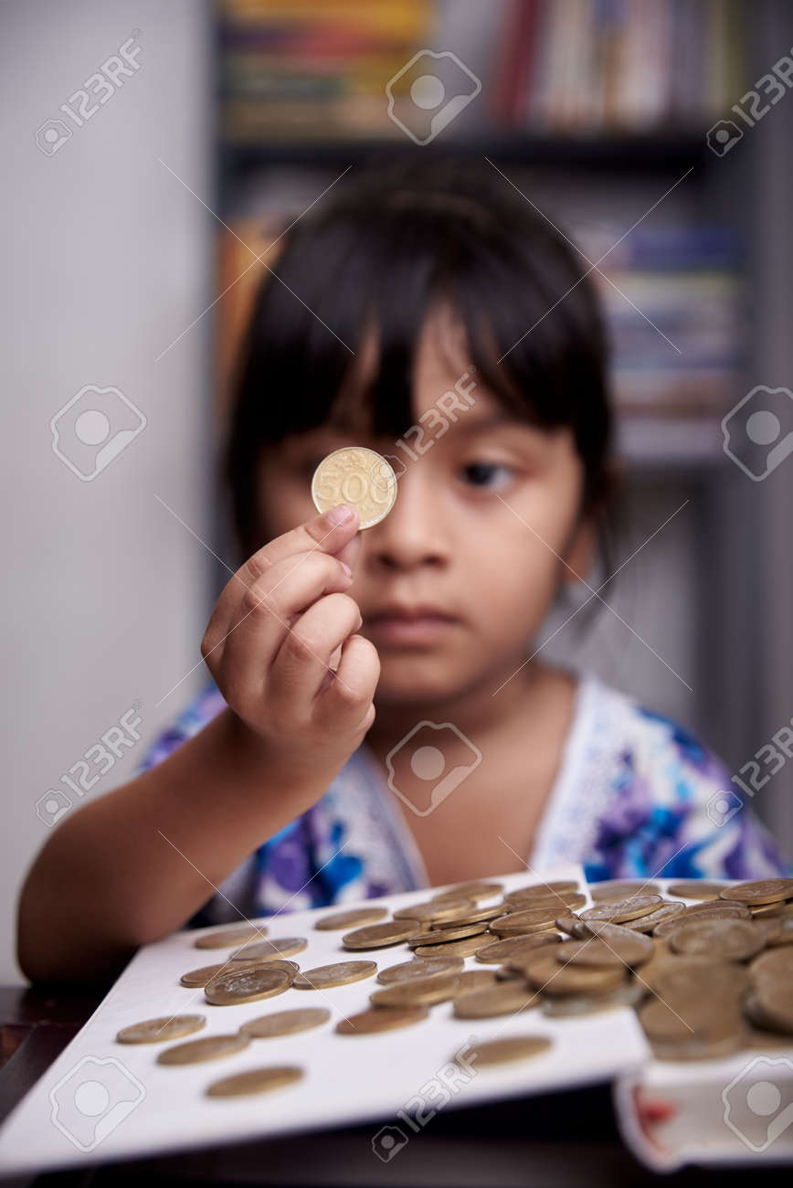Little cute Girl is counting bunch of coins - 168492801