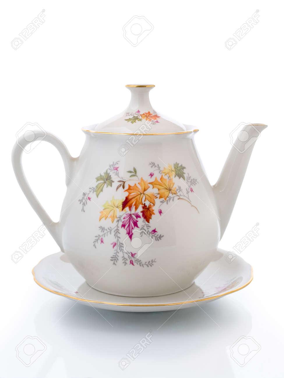 Weiße Teekanne weiße teekanne auf einer untertasse isoliert auf weiss beleuchtet