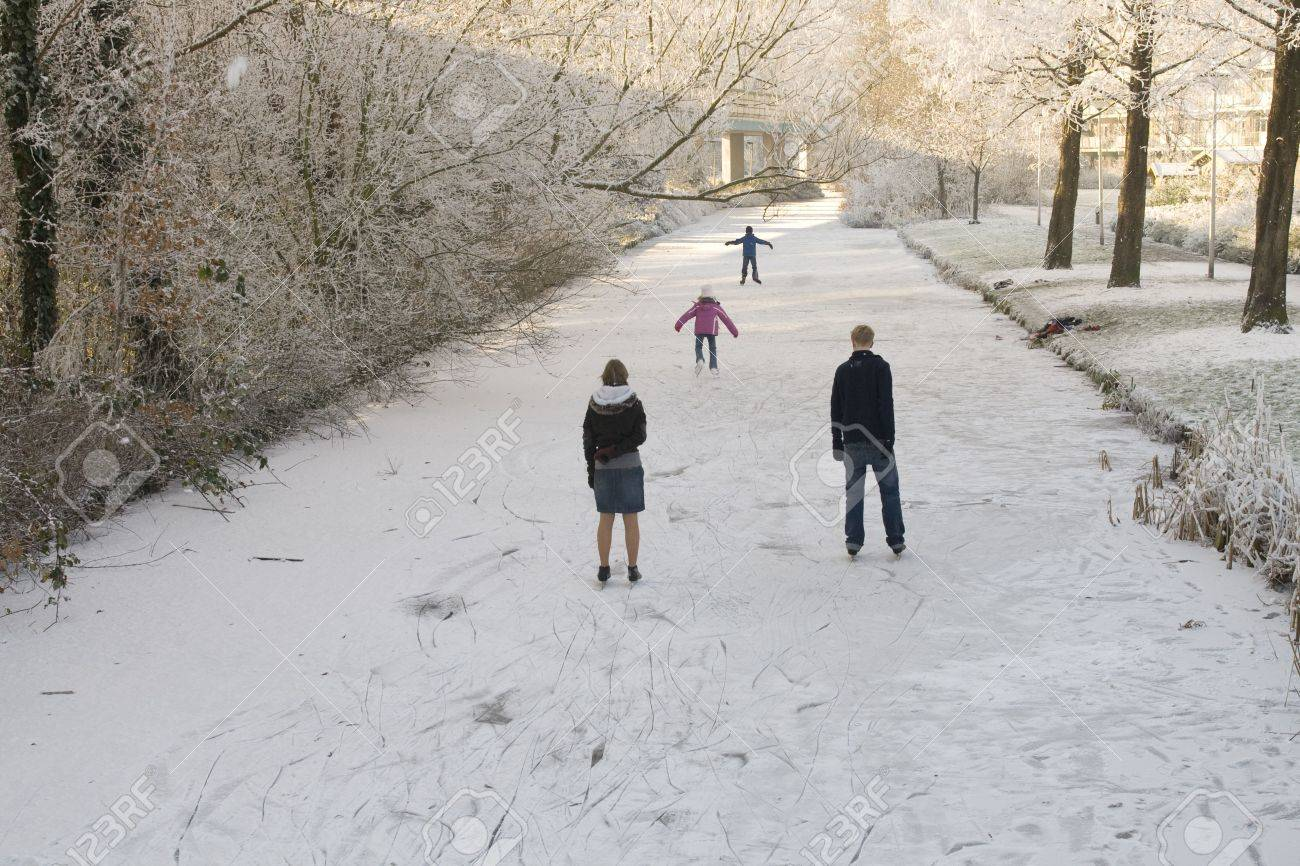 children and young people skating on a icy canal in the netherlands with sun through the trees Stock Photo - 2282635