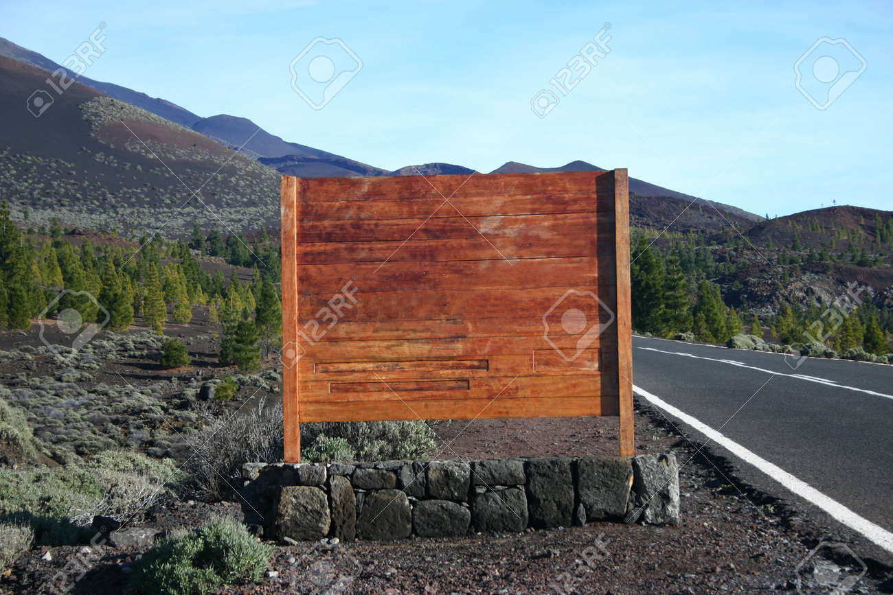 blank wooden sign next to asphalt road in volcanic landscape Stock Photo - 2313933