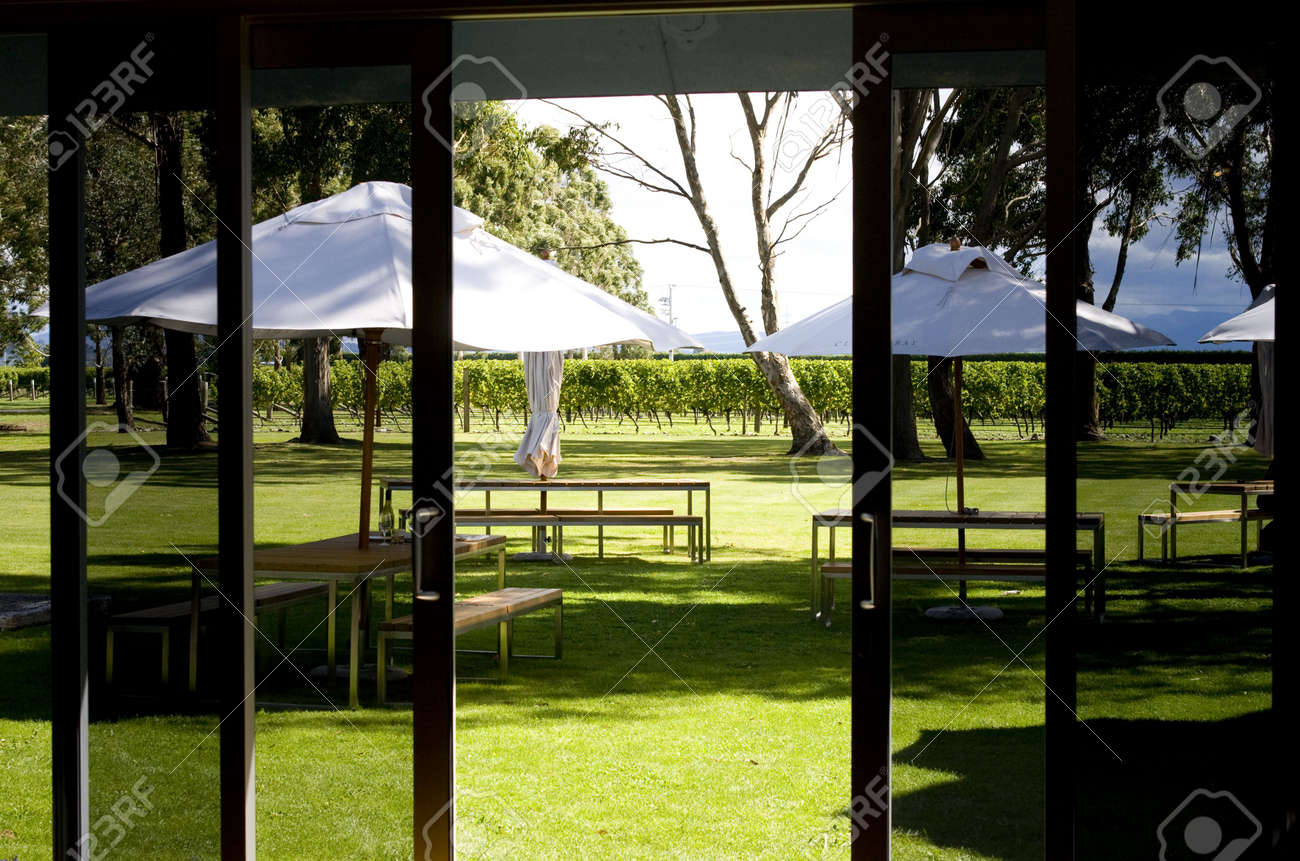 Picnic tables seen through sliding doors in sunny vineyard Stock Photo - 5106255