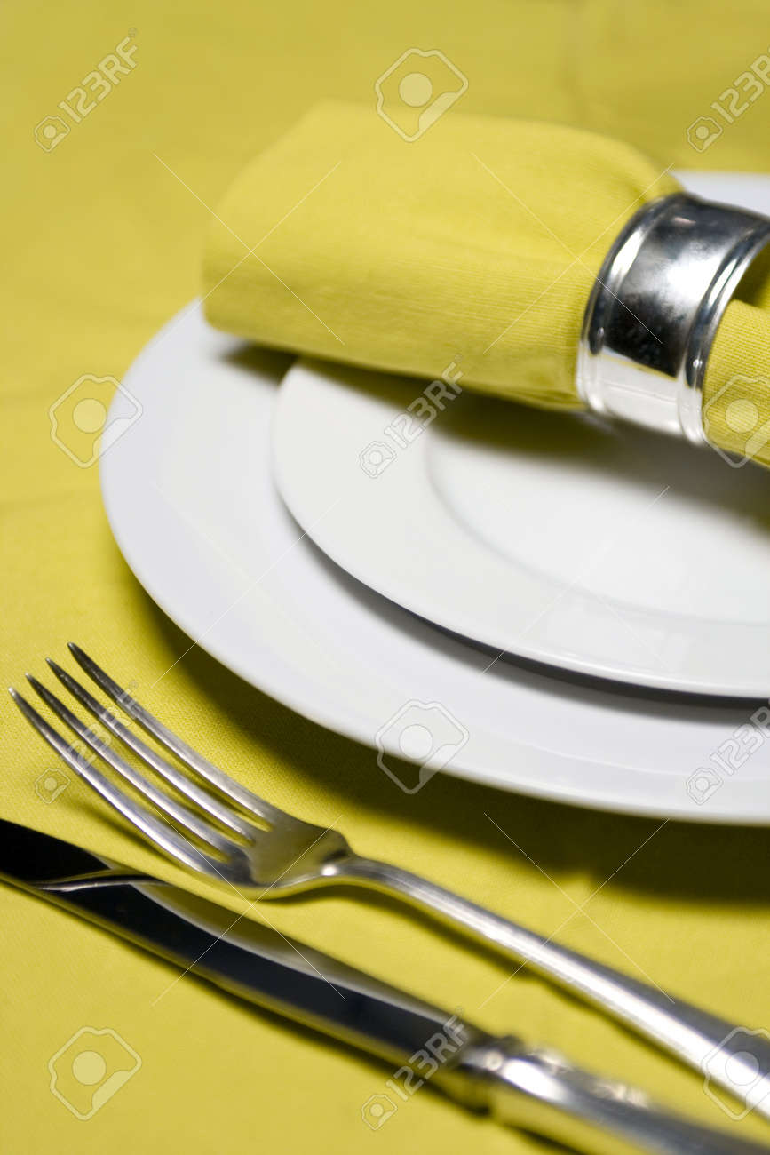 Table Setting With Napkin, Silverware And Plates On Yellow ...