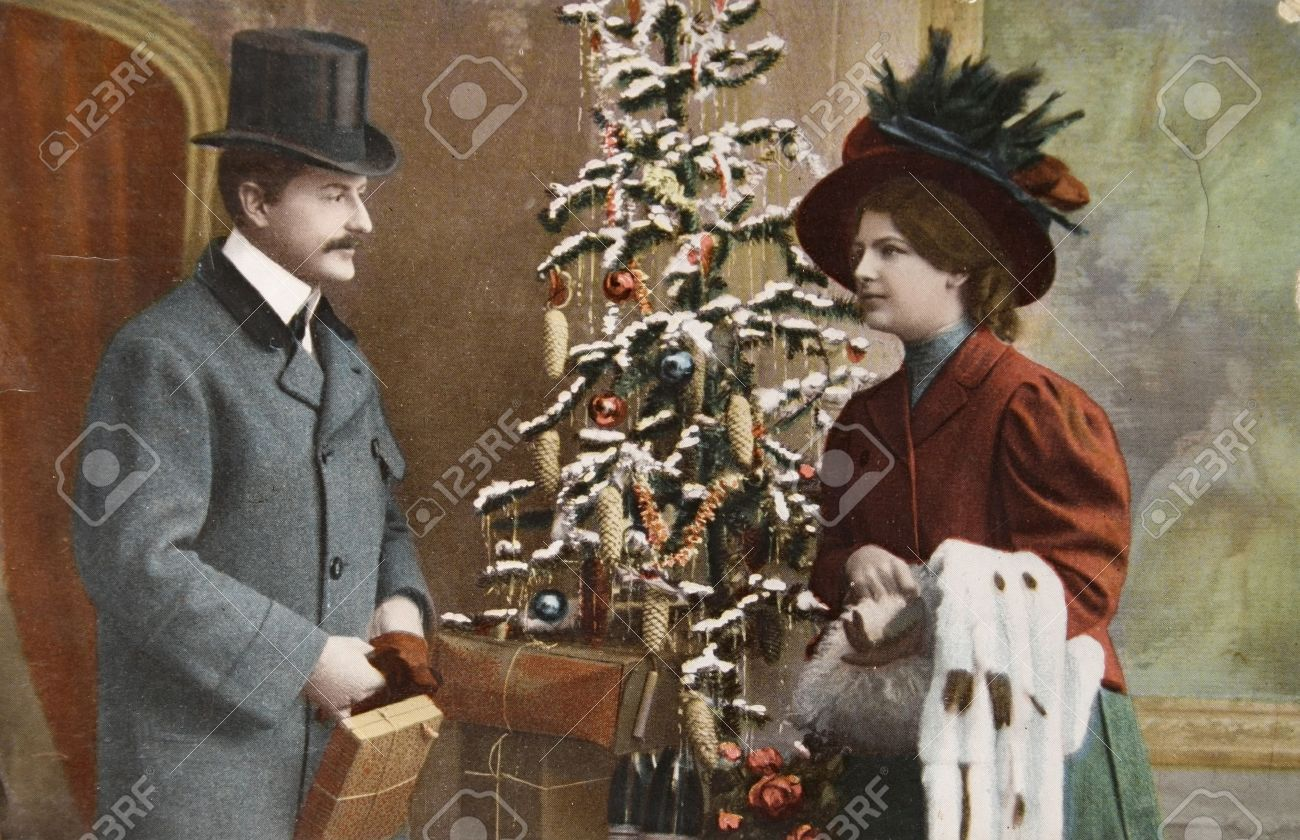 GERMANY- CIRCA 1915: Vintage christmas card printed in Germany in 1915 with loving couple beside a christmas tree  with presents, circa 1915.  Stock Photo - 10580868