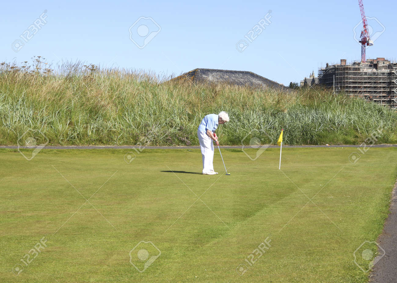 ST.ANDREWS, GREAT BRITAIN-JULY 24: Very old grey haired woman is playing golf at St. Andrews.on July 24,2011. Golf is a sport you can maintain up untill a very old age.  Stock Photo - 10738836