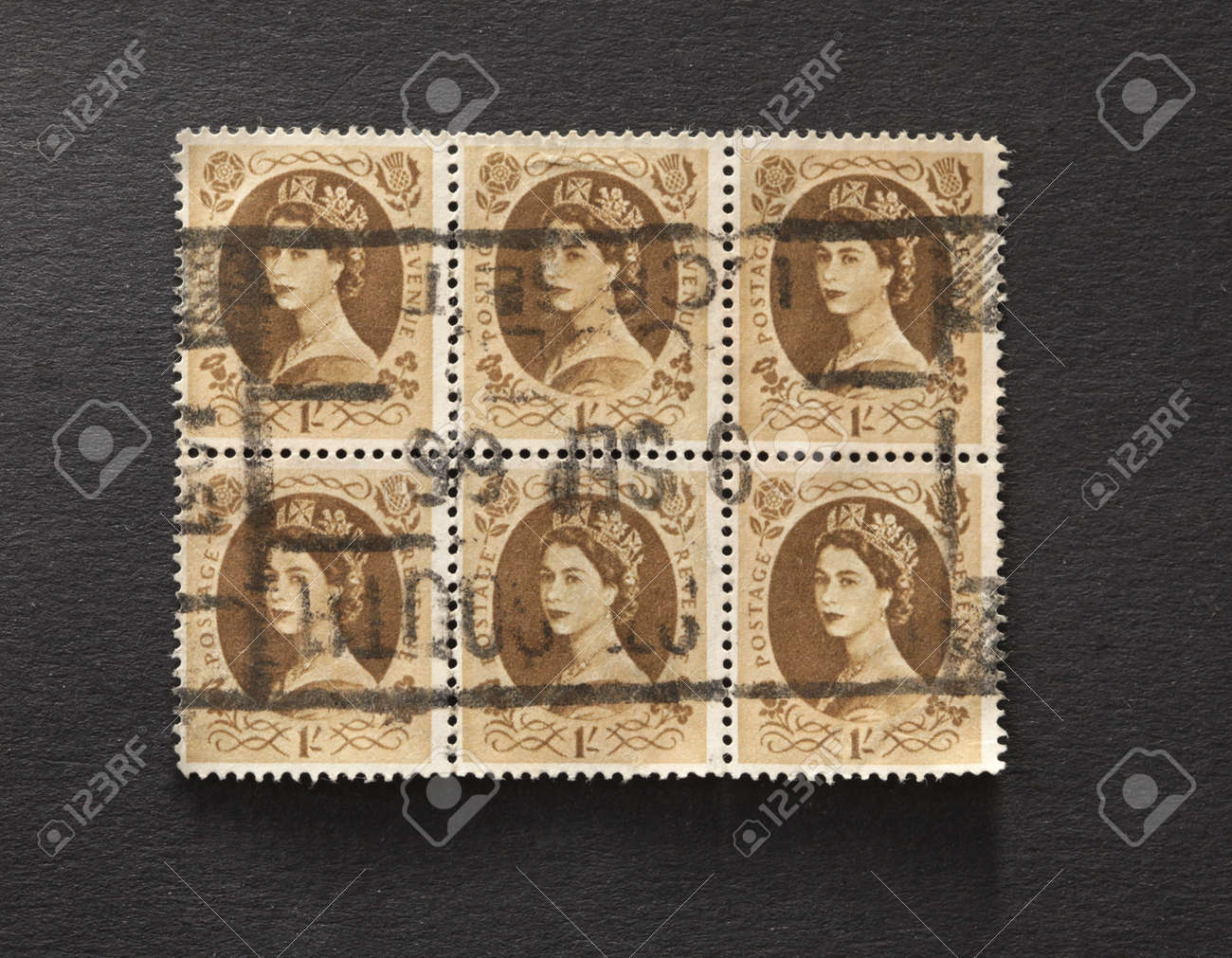 UNITED KINGDOM - CIRCA 1952 to 1965: Six English One Shilling Brown Used Postage Stamps on a block  showing Portrait of Queen Elizabeth 2nd, circa 1952 to 1965  Stock Photo - 11970897