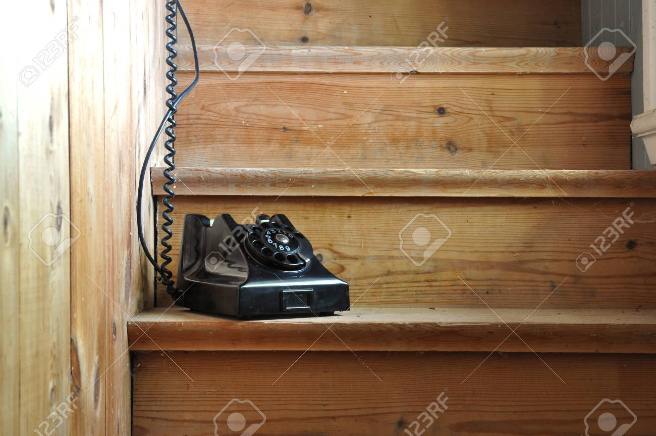 Old bakelite phone on a wooden staircase with a hidden receiver. Stock Photo - 15259179