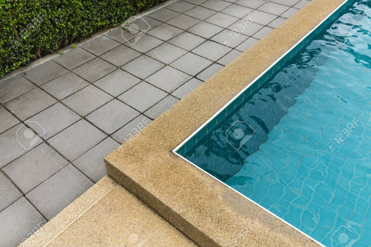 Swimming pool with cement blocks pathway and polished stone floor
