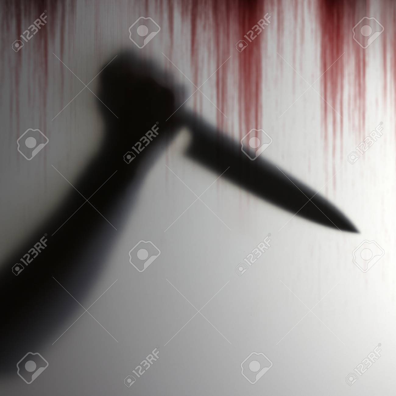 Shadow of hand holding knife to pierce the victim behind a transparent object with bloody background scary - 93464902