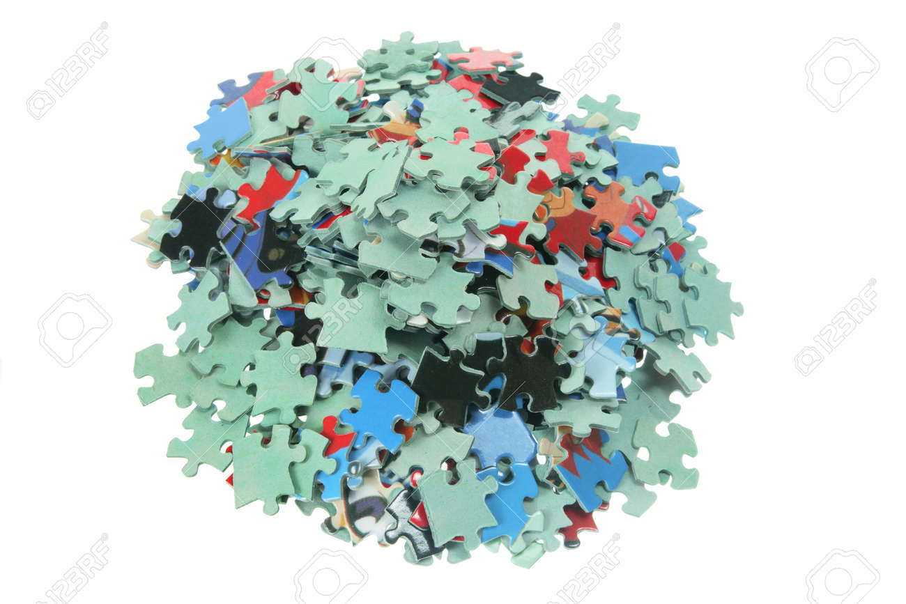 Pile Of Jigsaw Puzzle Pieces On White Background Stock Photo