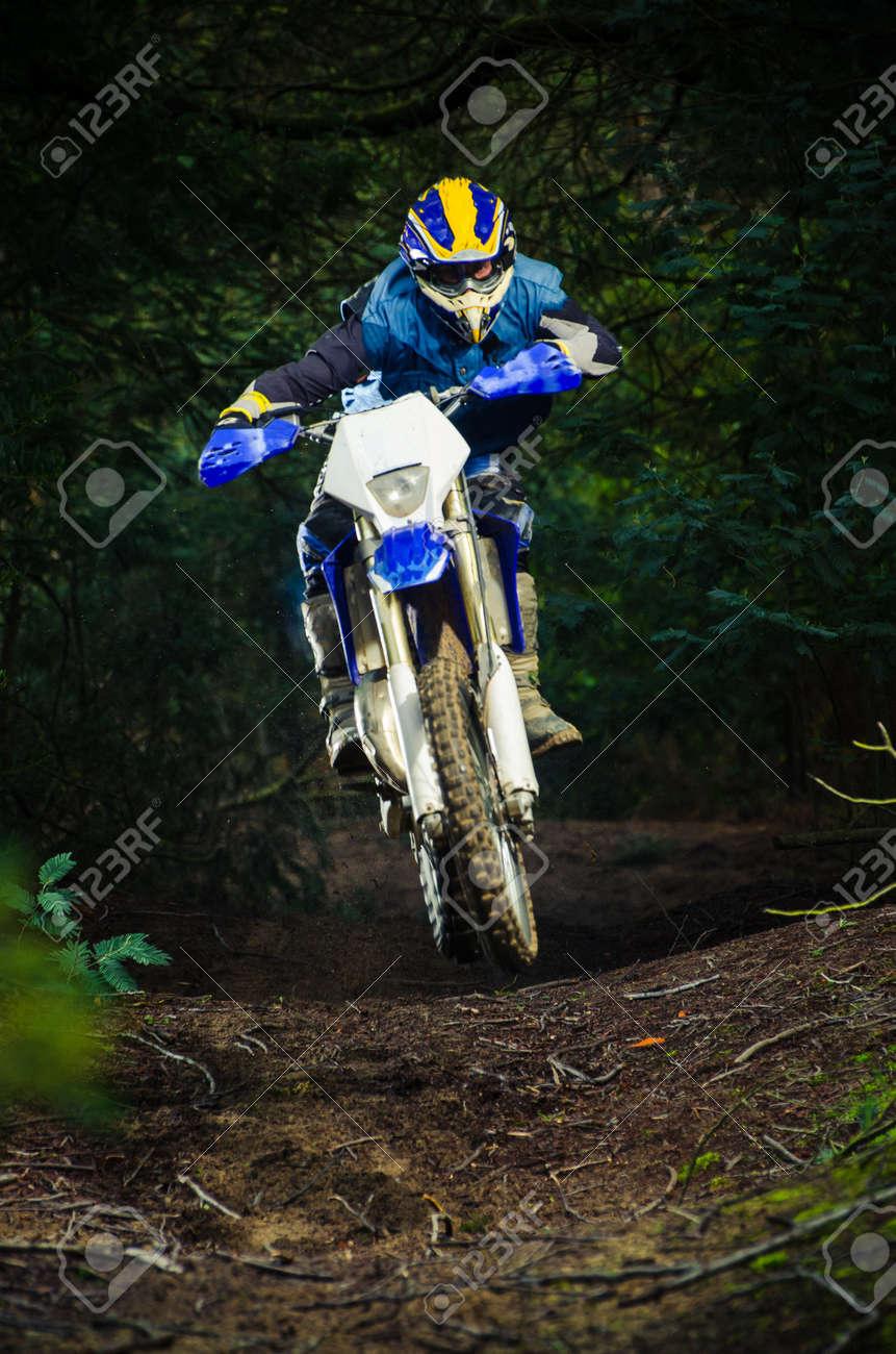 Enduro bike rider on action. Small jamp on muddy terrain. Stock Photo - 16711246