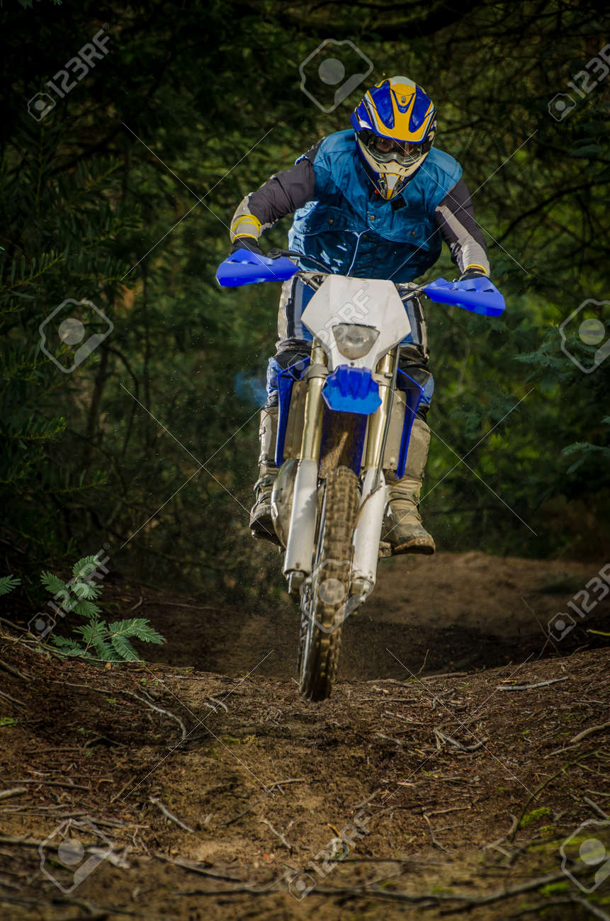 Enduro bike rider on action. Small jamp on muddy terrain. - 17032888