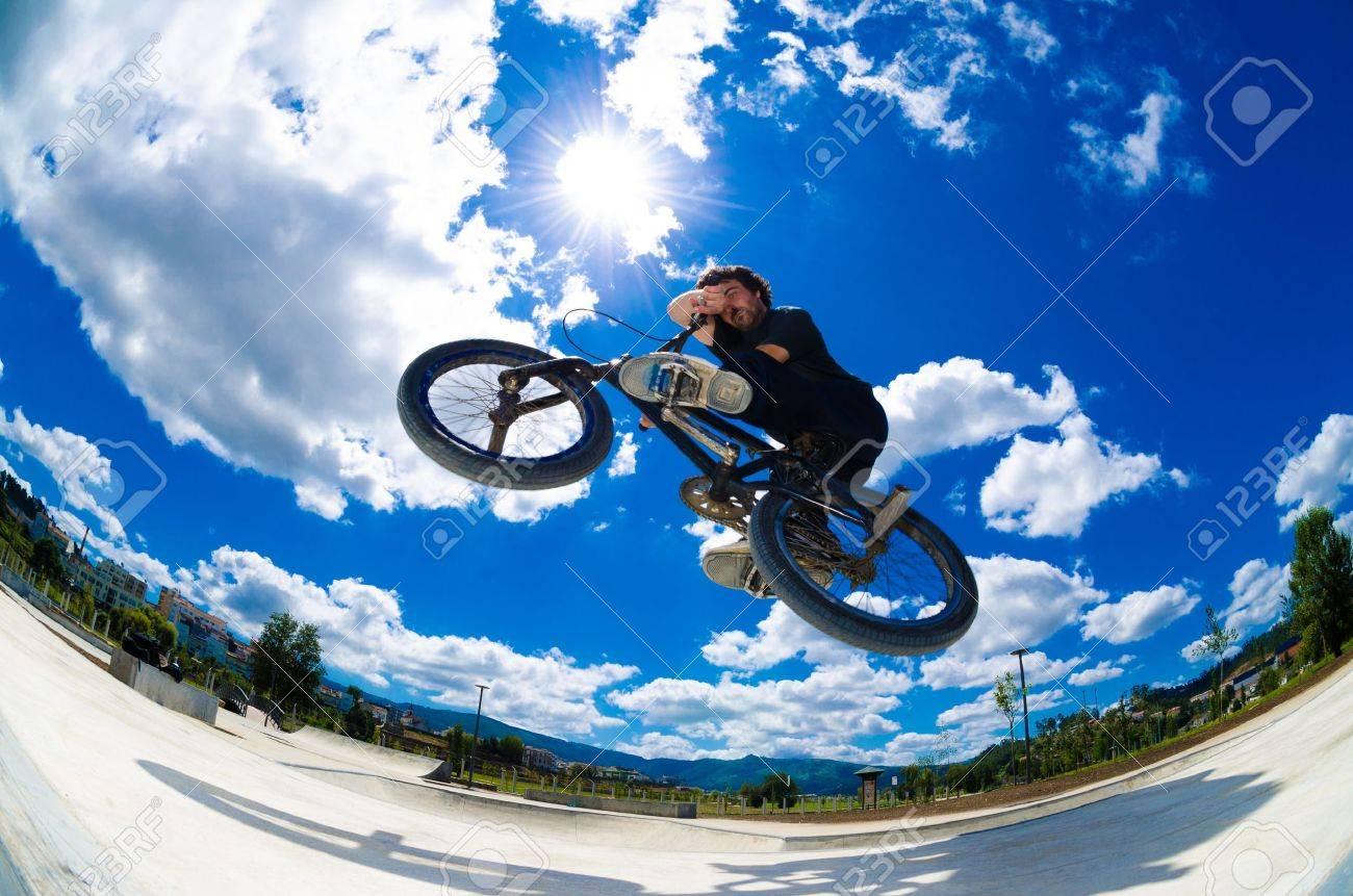BMX rider jumps while doing cross bar trick. - 17231134