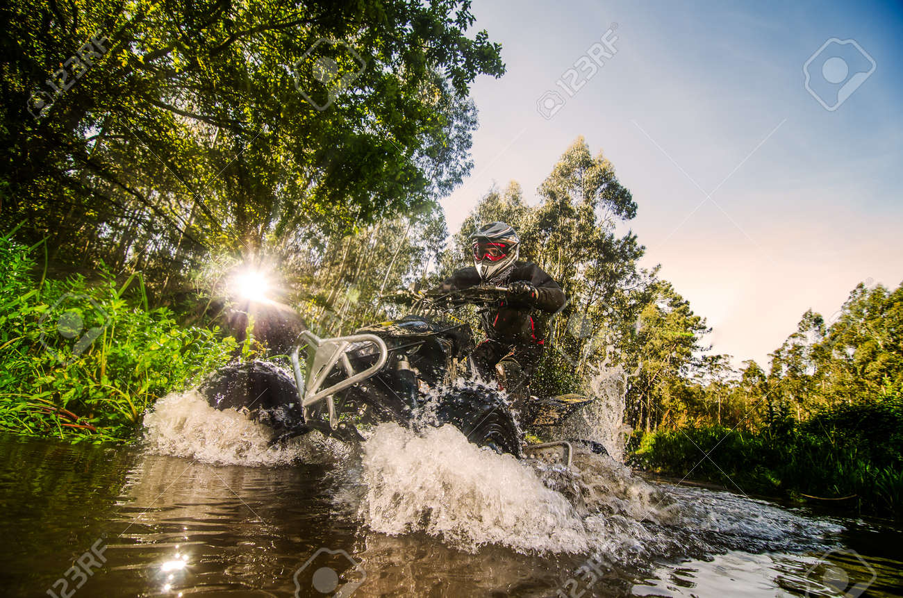 Quad rider through water stream in the forest against sunlight. - 19224029