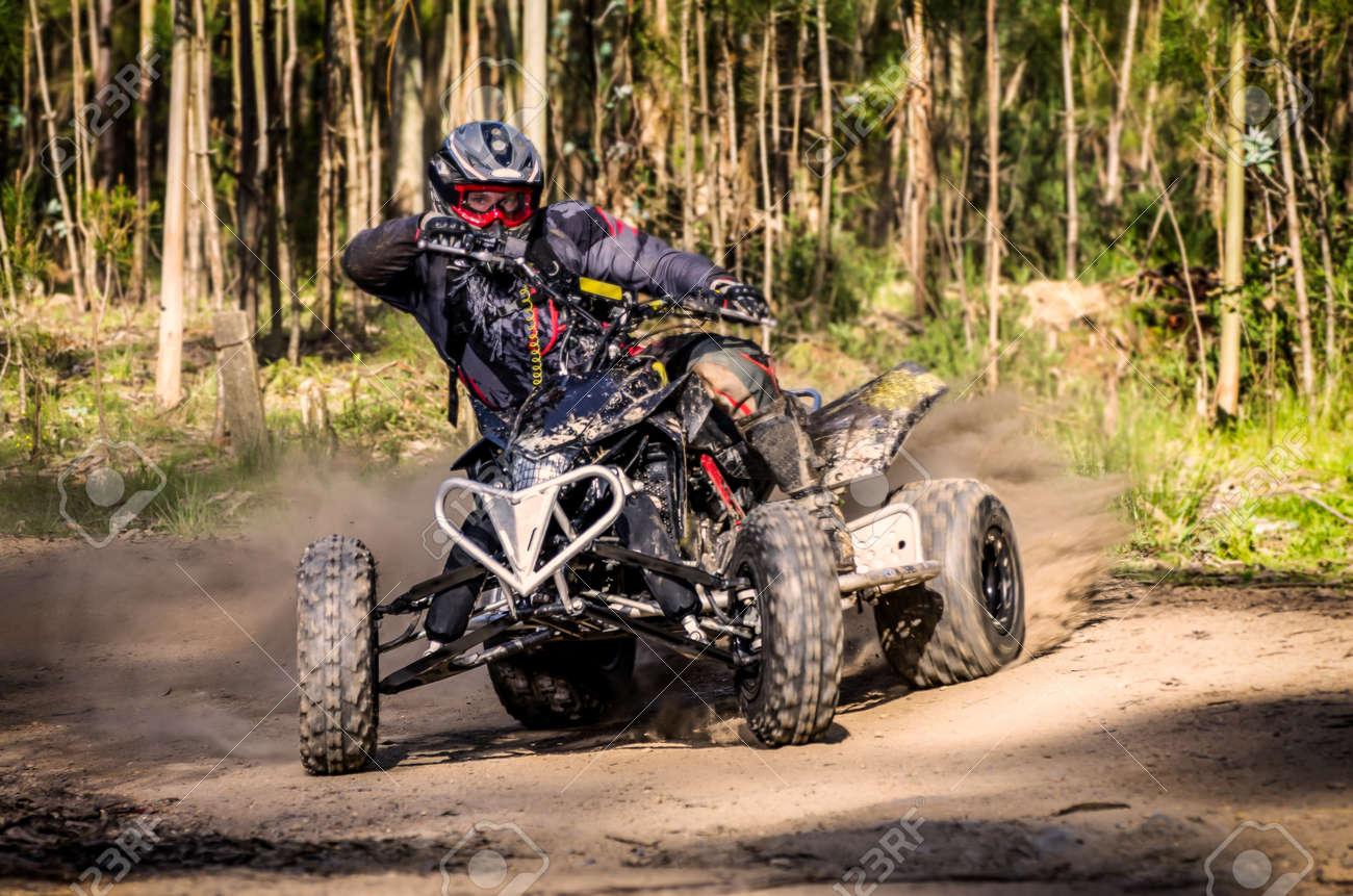 ATV racer takes a turn during a race on a dusty terrain. - 19223932