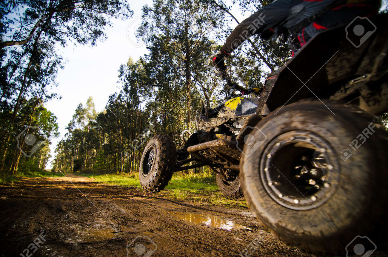 Quad rider jumping on a muddy forest trail. - 21174410
