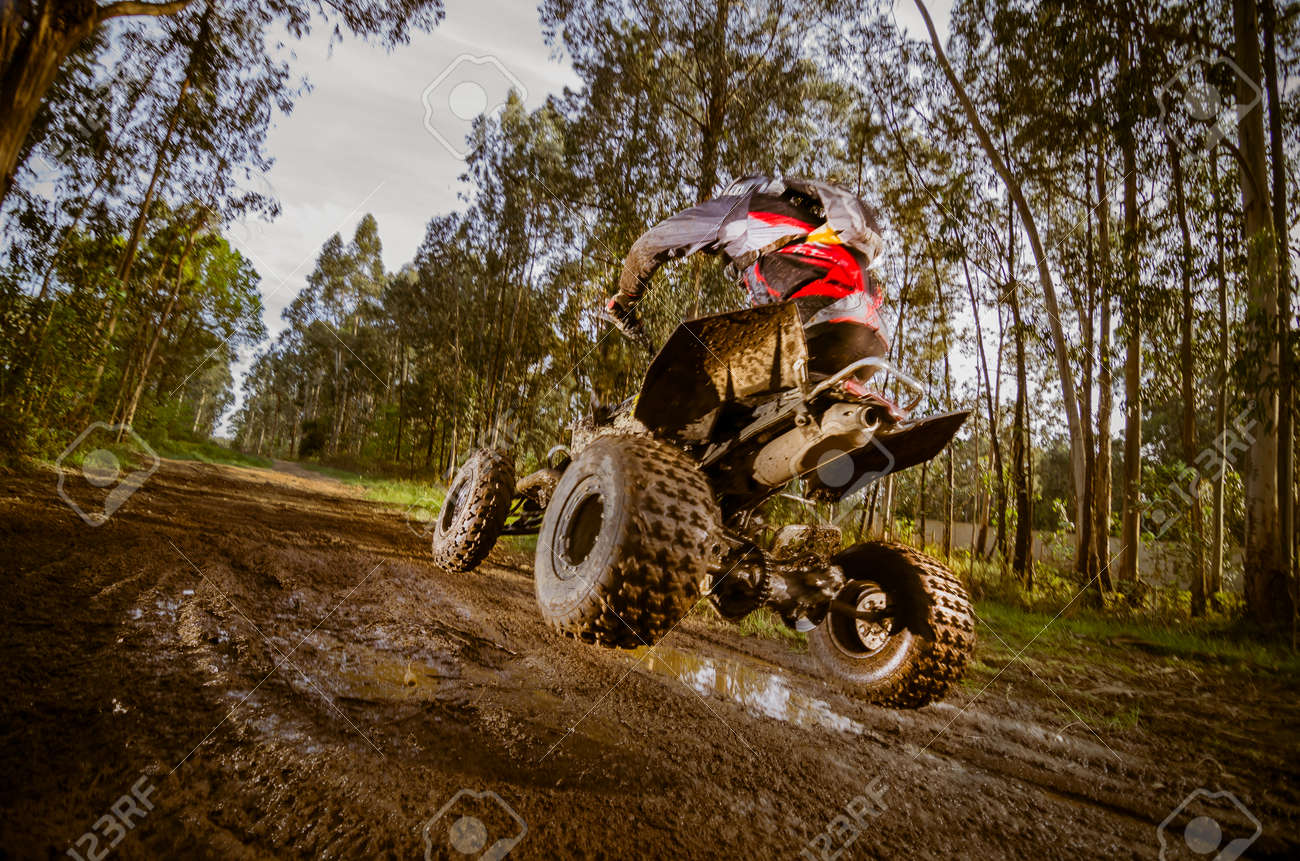 Quad rider jumping on a muddy forest trail. - 28117041