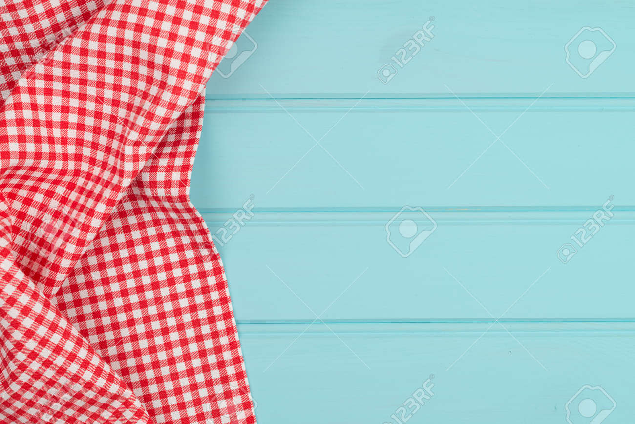 White and red towel over wooden kitchen table. View from above. - 39634388