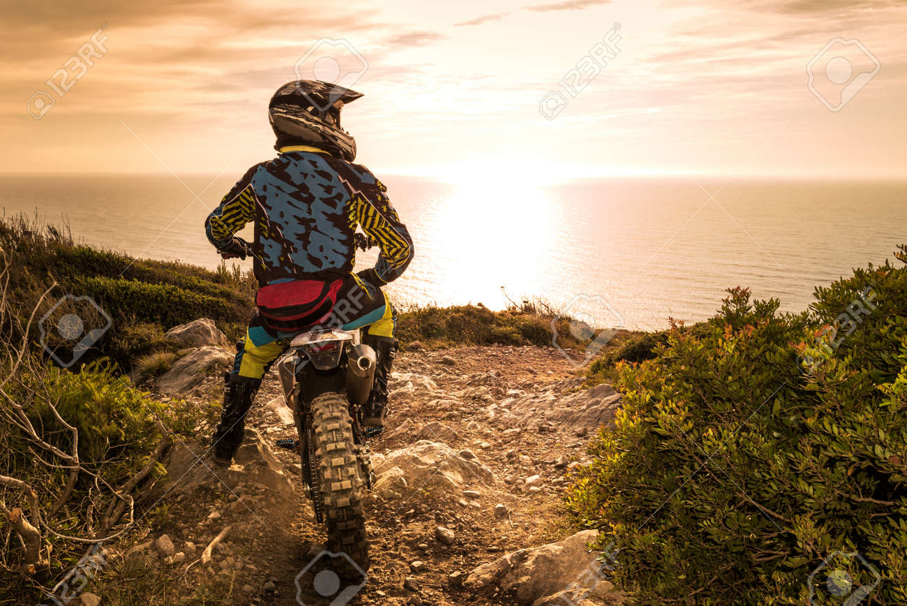 Enduro racer sitting on his motorcycle watching the sunset. - 40309101