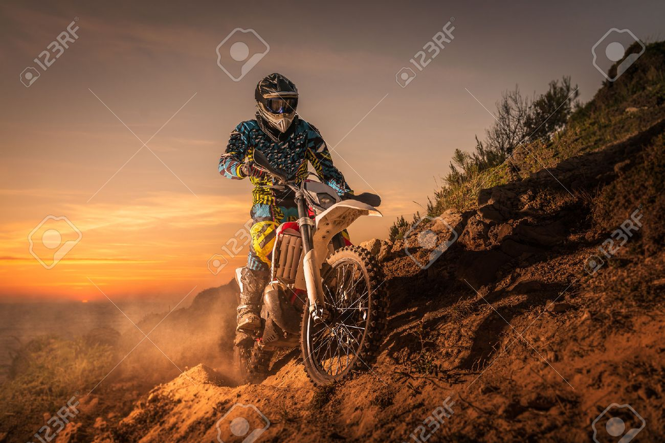 enduro rider climbing a high slope against a beautiful sunset on a seascape. - 40309102