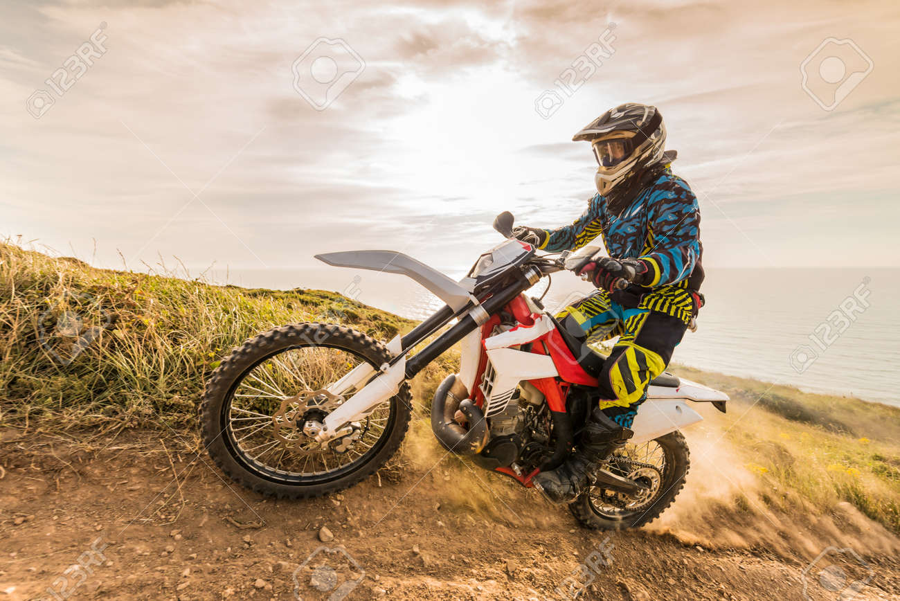 Enduro rider climbing a steep slope against a beautiful sunset on a seascape - 40479761