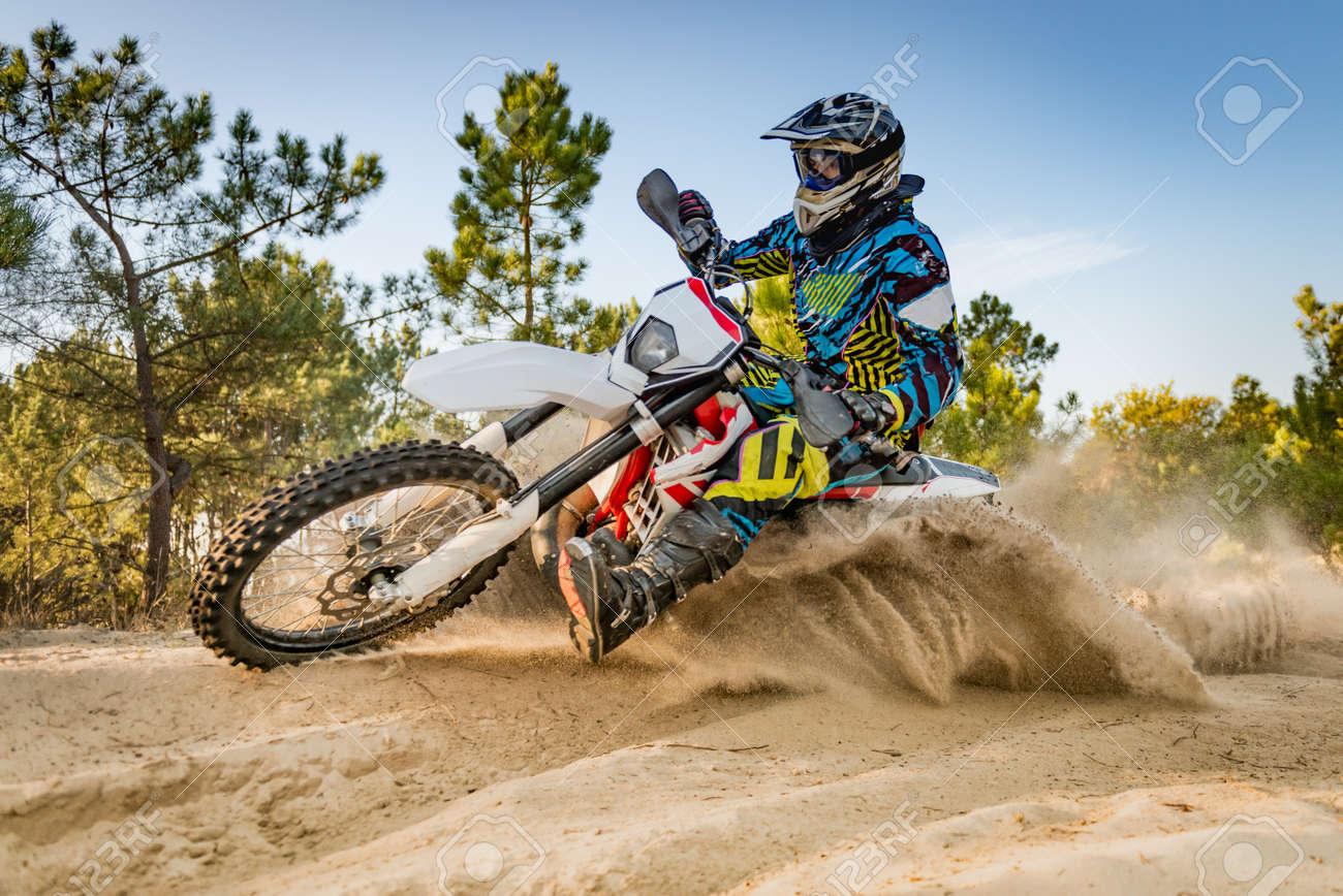 Enduro bike rider on action. Turn on sand terrain. - 48072704