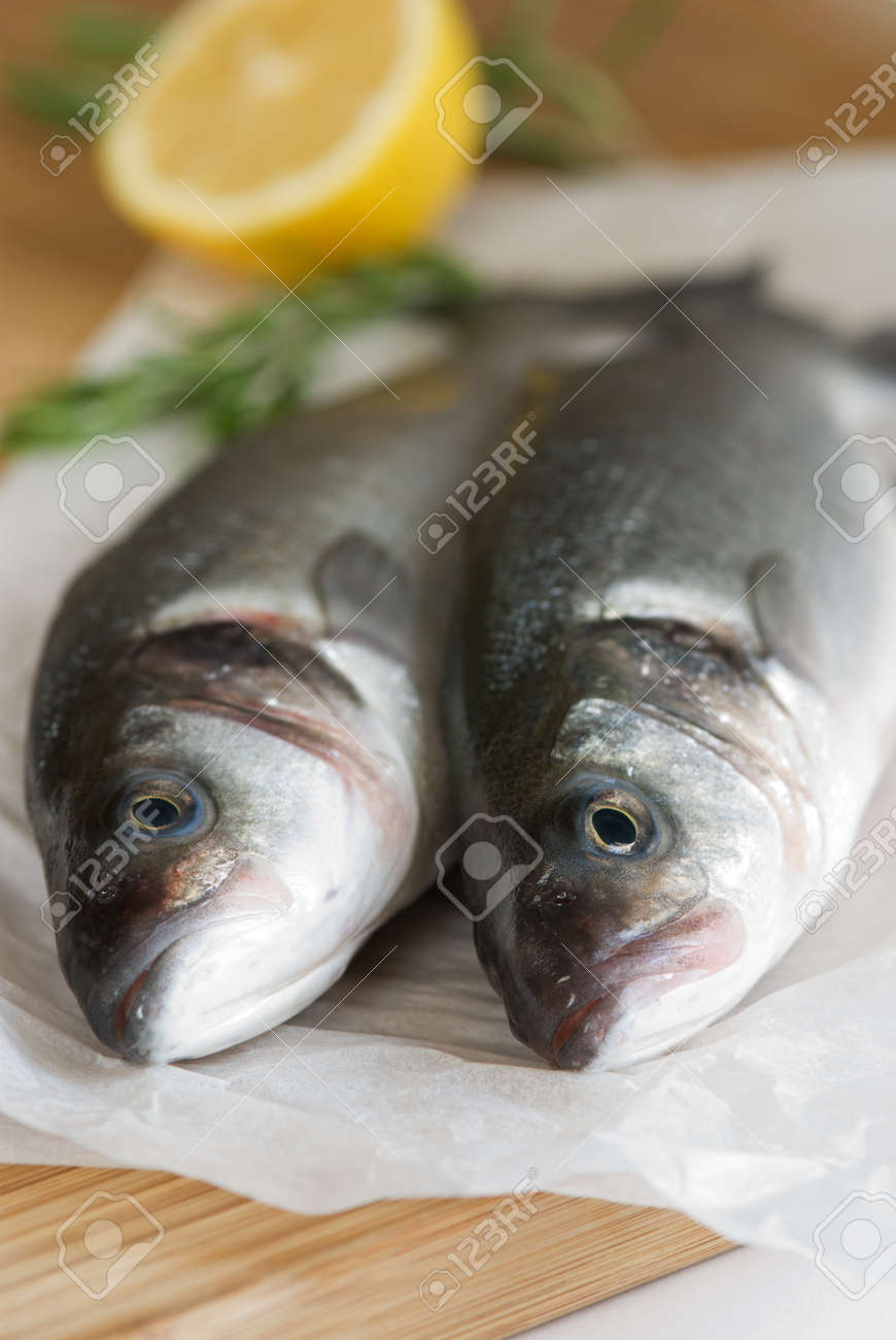 Two fresh sea bass with lemon and rosemary Stock Photo - 8474594