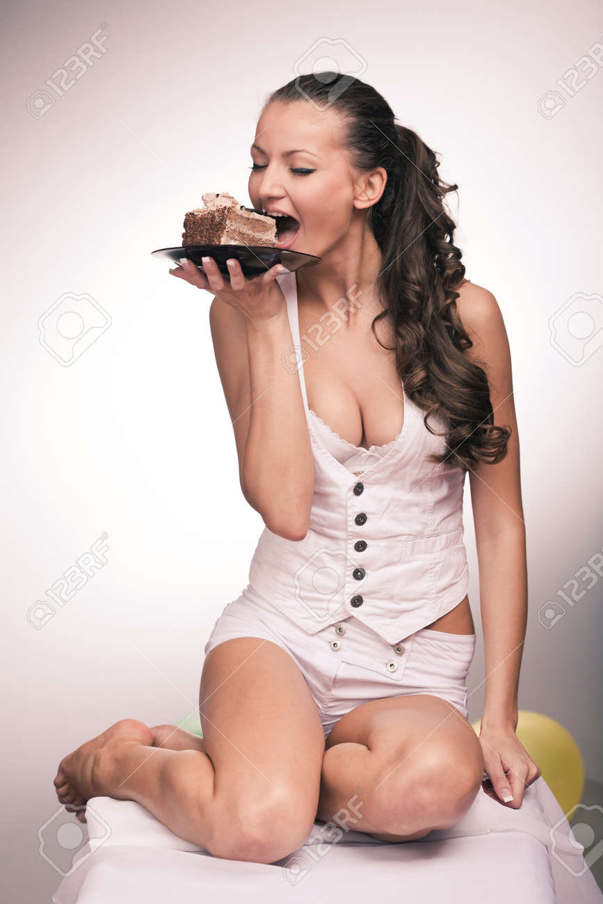 Portrait of young pretty girl with a cake and balloons in background Stock Photo - 11251155