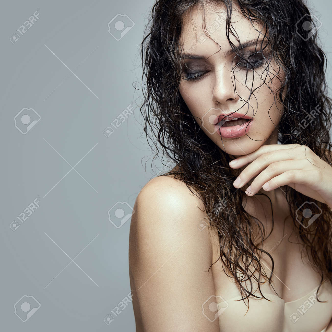 fashion portrait of young gorgeous brunette with wet hair stock