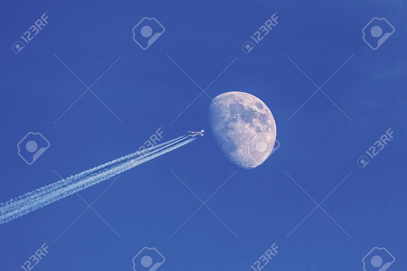 Modern jet plane with moon on blue sky as background, making illusion of space shuttle flying to the moon. - 104890710