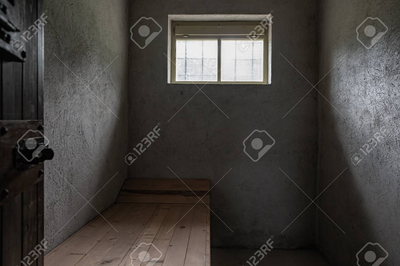 Small prison concrete cell with one small window and one wooden pallet. - 105230579