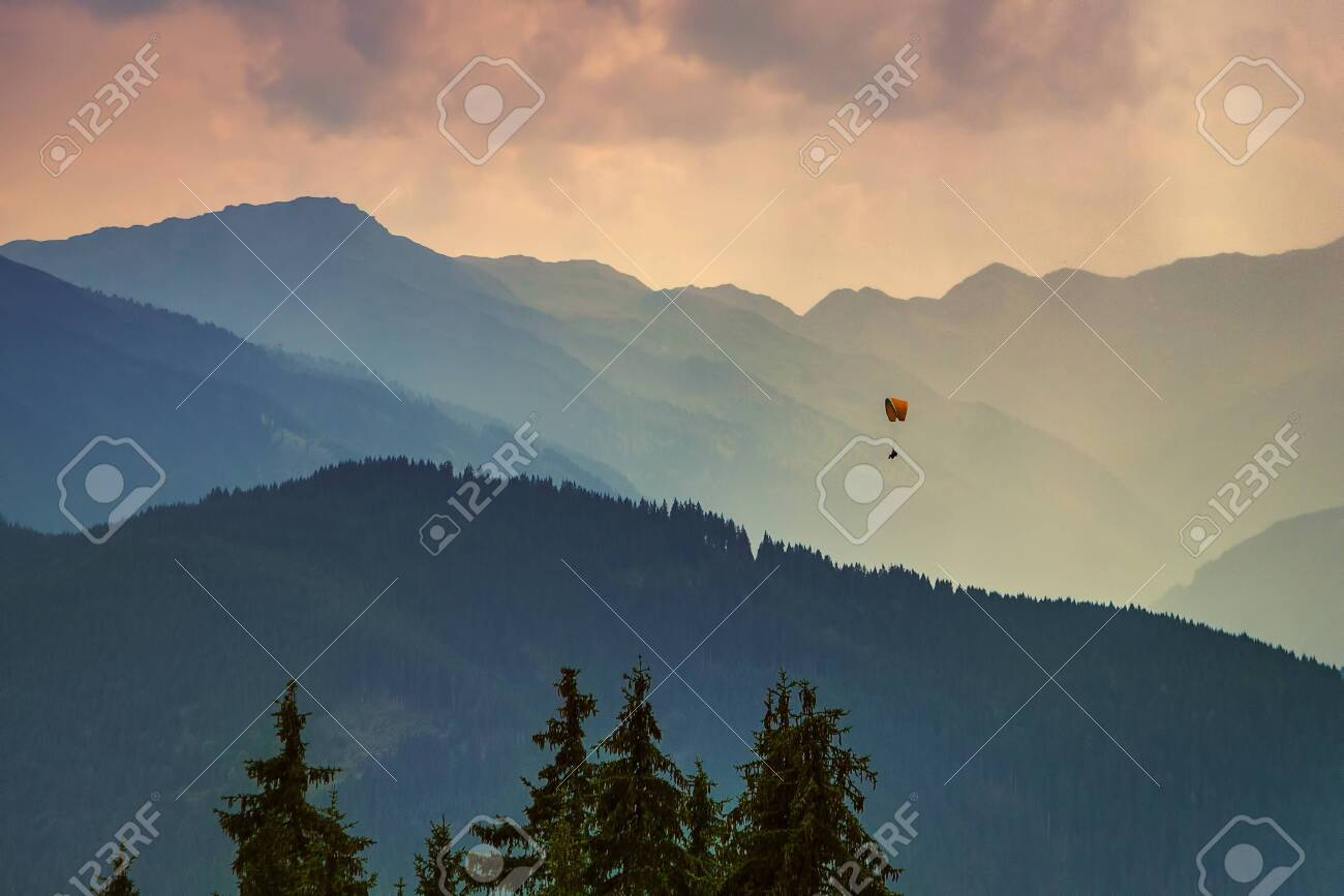Moody picture of evening mountain ridges, Austrian alps, with a small paraglider on a horizon. - 128379512
