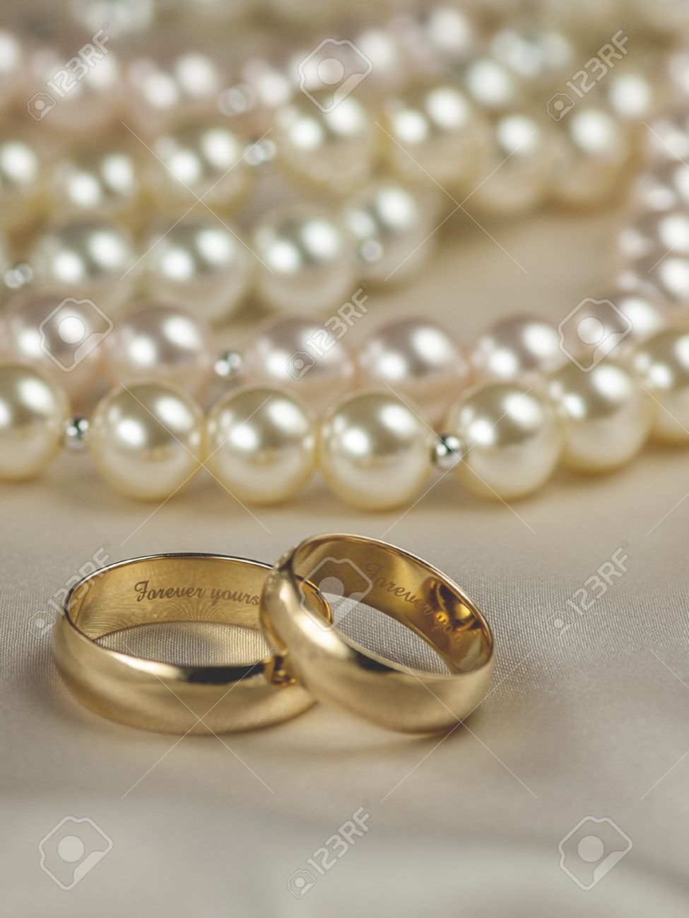 Pair Of Gold Wedding Rings With Pearl Background; Focus On Interior Ring  Engraving: Forever