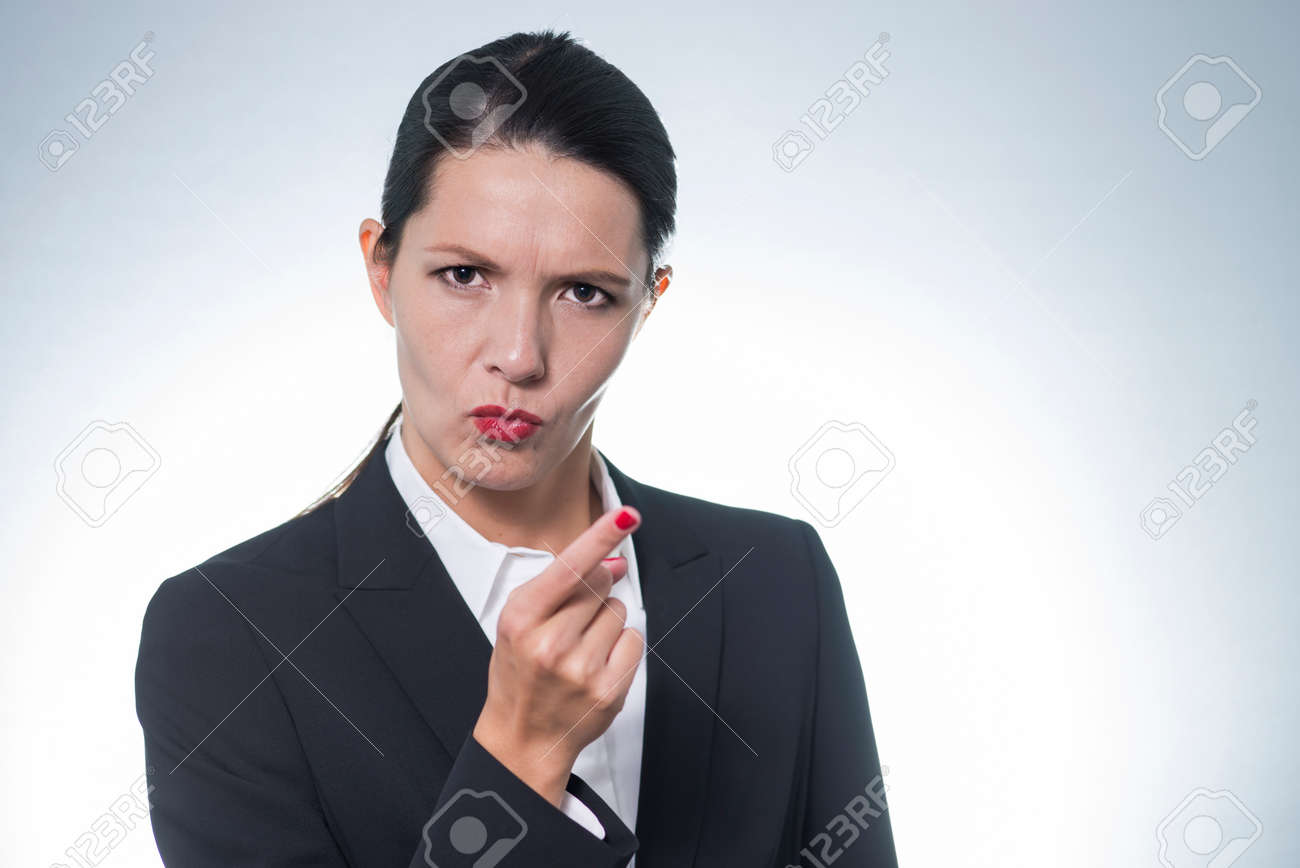 Stern young business woman or manageress making a finger gesture