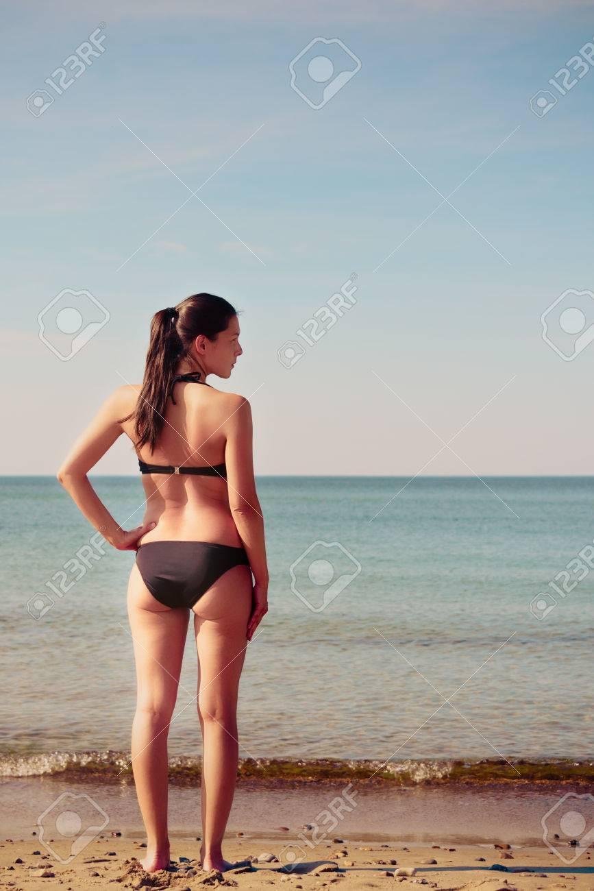 5f79002529a1 Mujer joven delgada bien proporcionada en un bikini de pie en la playa, de  espaldas a la cámara en el sol de verano con vistas al mar en calma que ...
