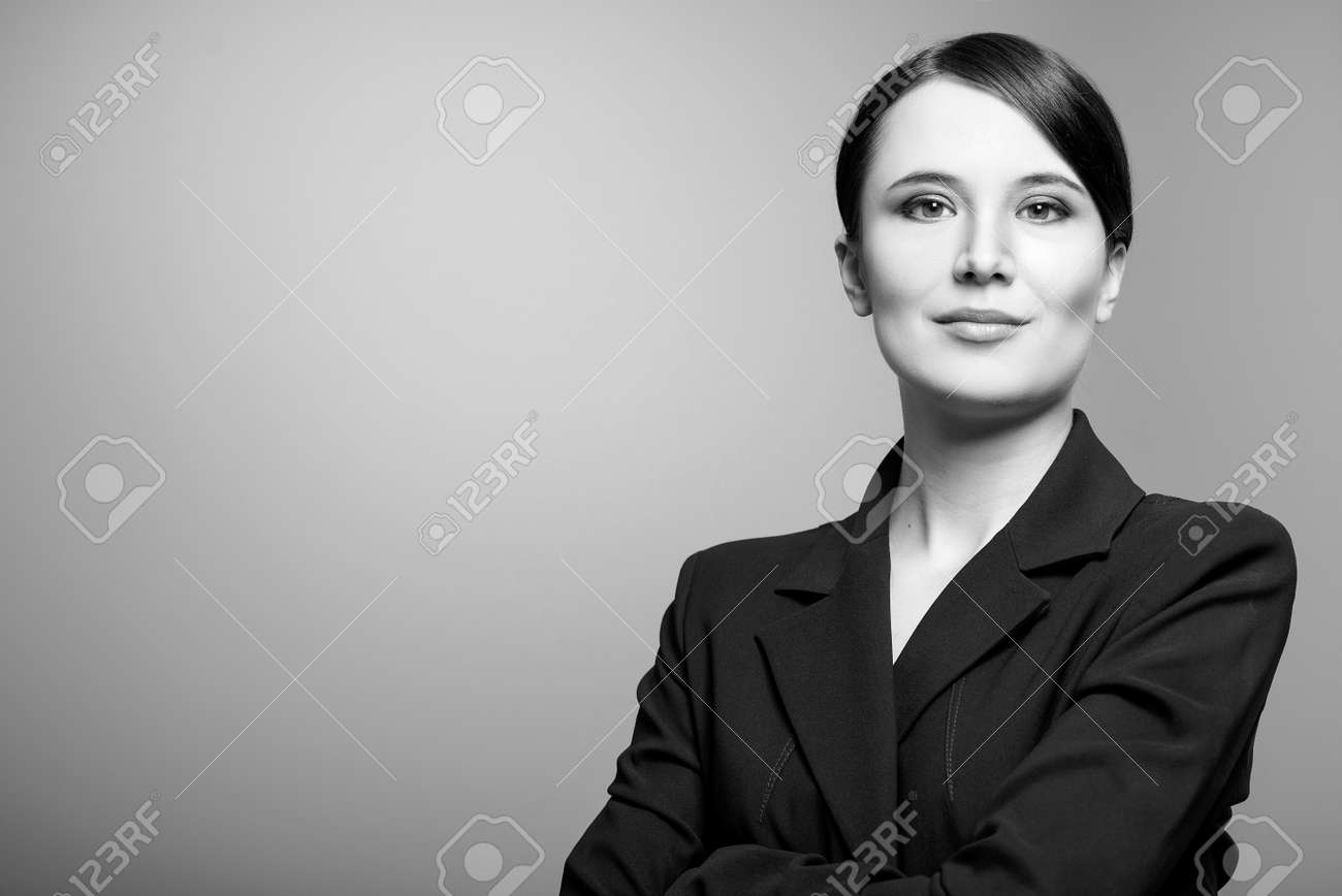 Black and white portrait of a beautiful elegant professional woman standing with folded arms in a
