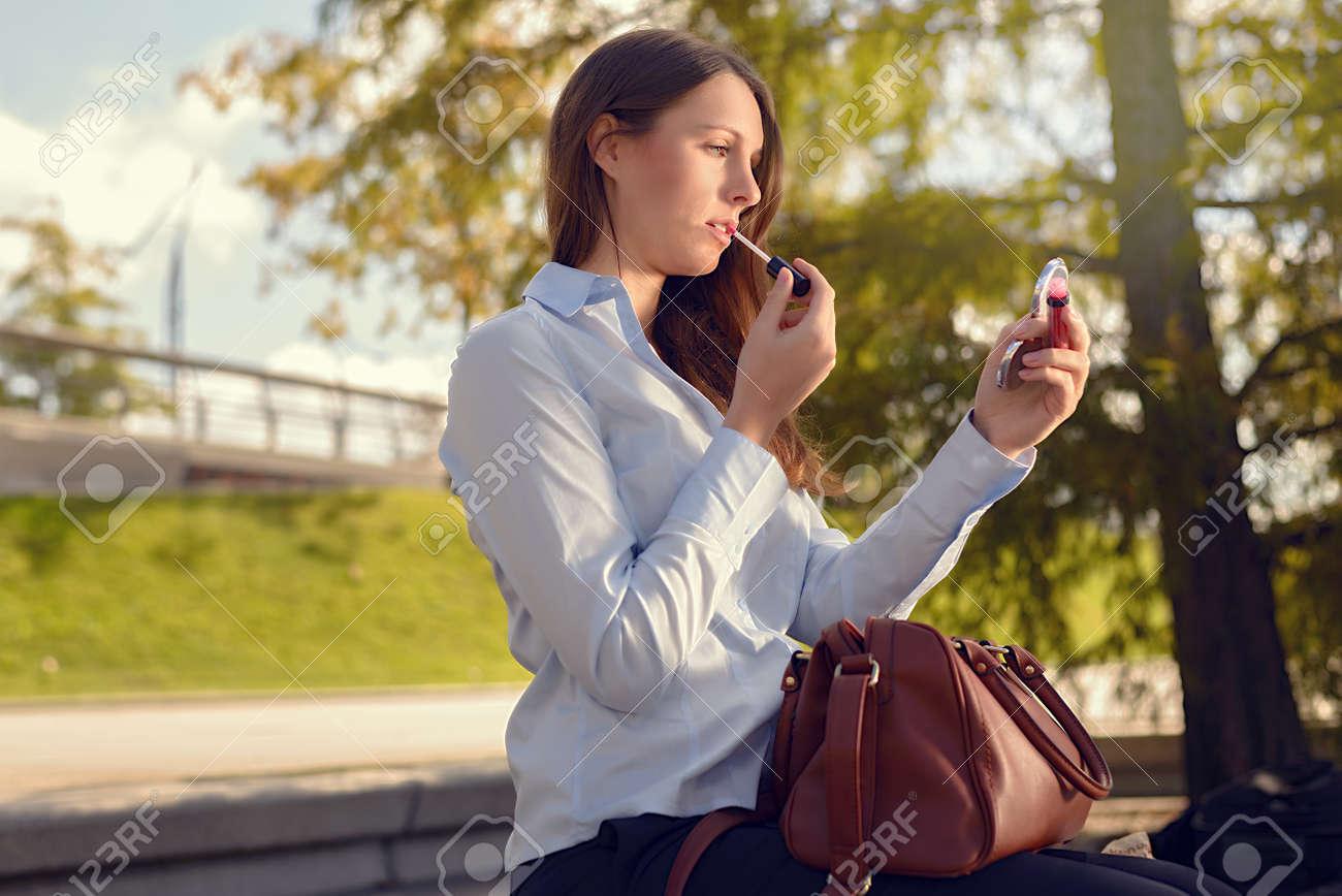 Mujer joven y atractiva refrescante su maquillaje en la calle aplicar el lápiz labial con el uso de un pequeño espejo de mano de su gran bolso de mano
