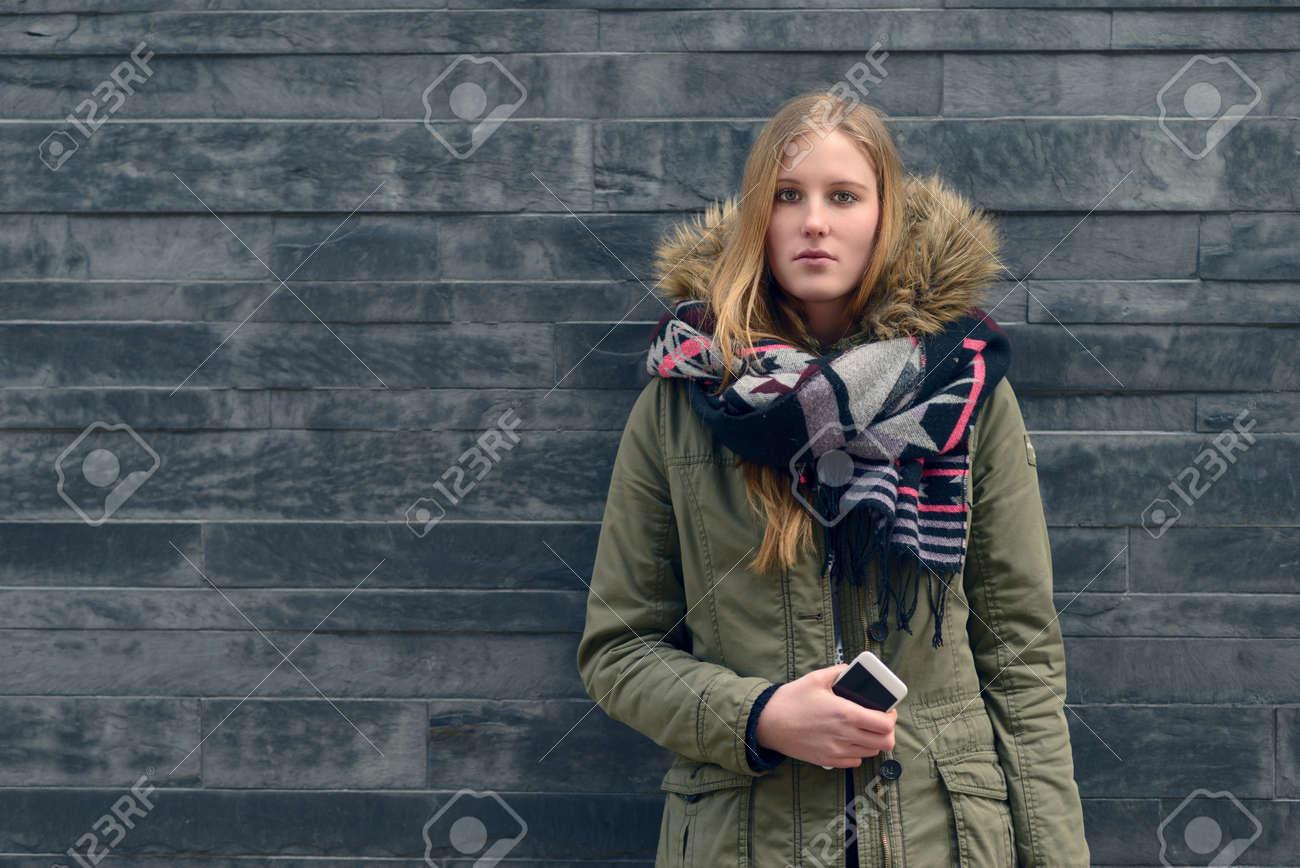 Banque d\u0027images , La mode jeune femme en hiver Outfit posant devant Vieux  Mur Gris tout en regardant la caméra.