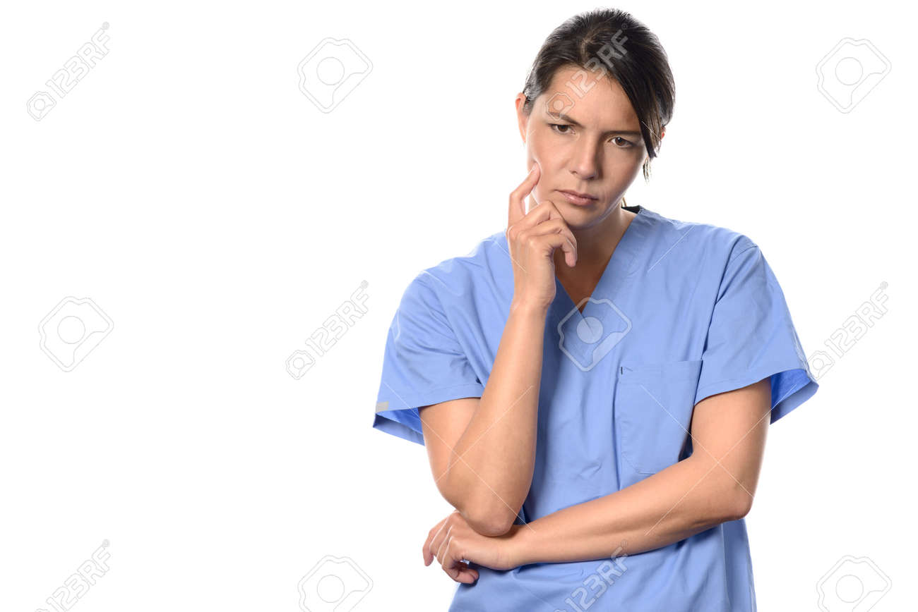 fe4e8461cb6 Despondent young female doctor or nurse wearing blue surgical scrubs  staring morosely at the floor with