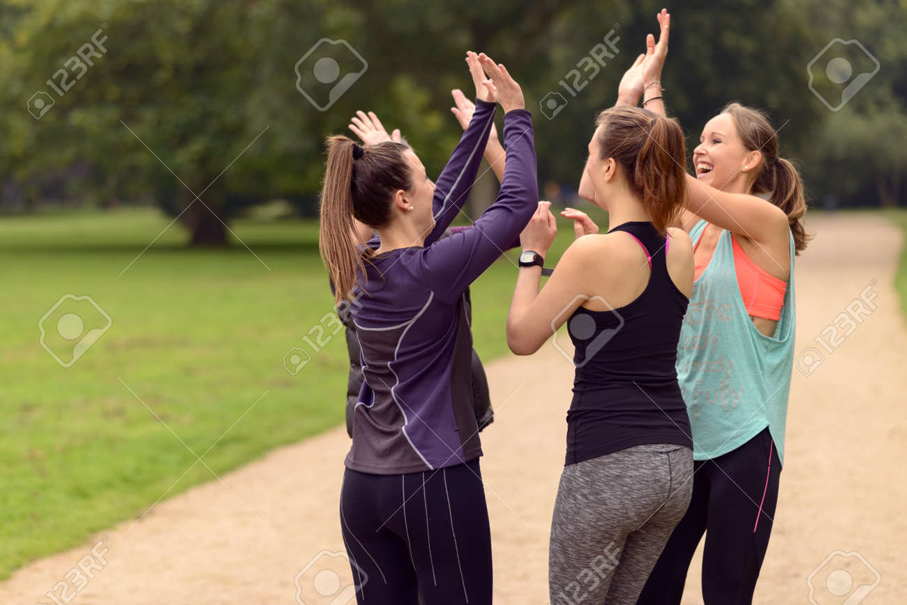 Four Happy Healthy Women Giving Double High Five Gesture While Relaxing After an Outdoor Exercise at the Park. - 45518570