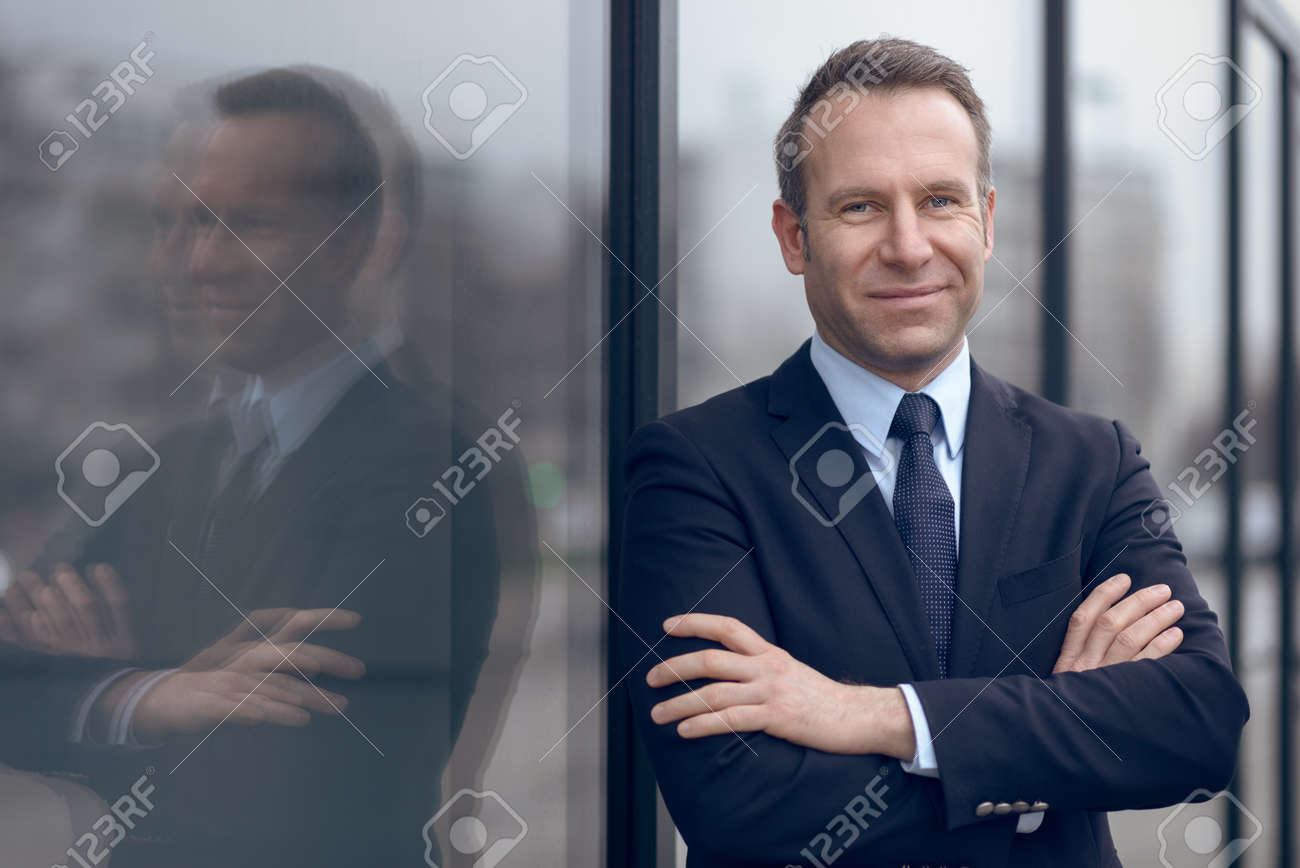 Single confident and handsome male businessman in blue suit and necktie with grin leaning on window outdoors - 52528469