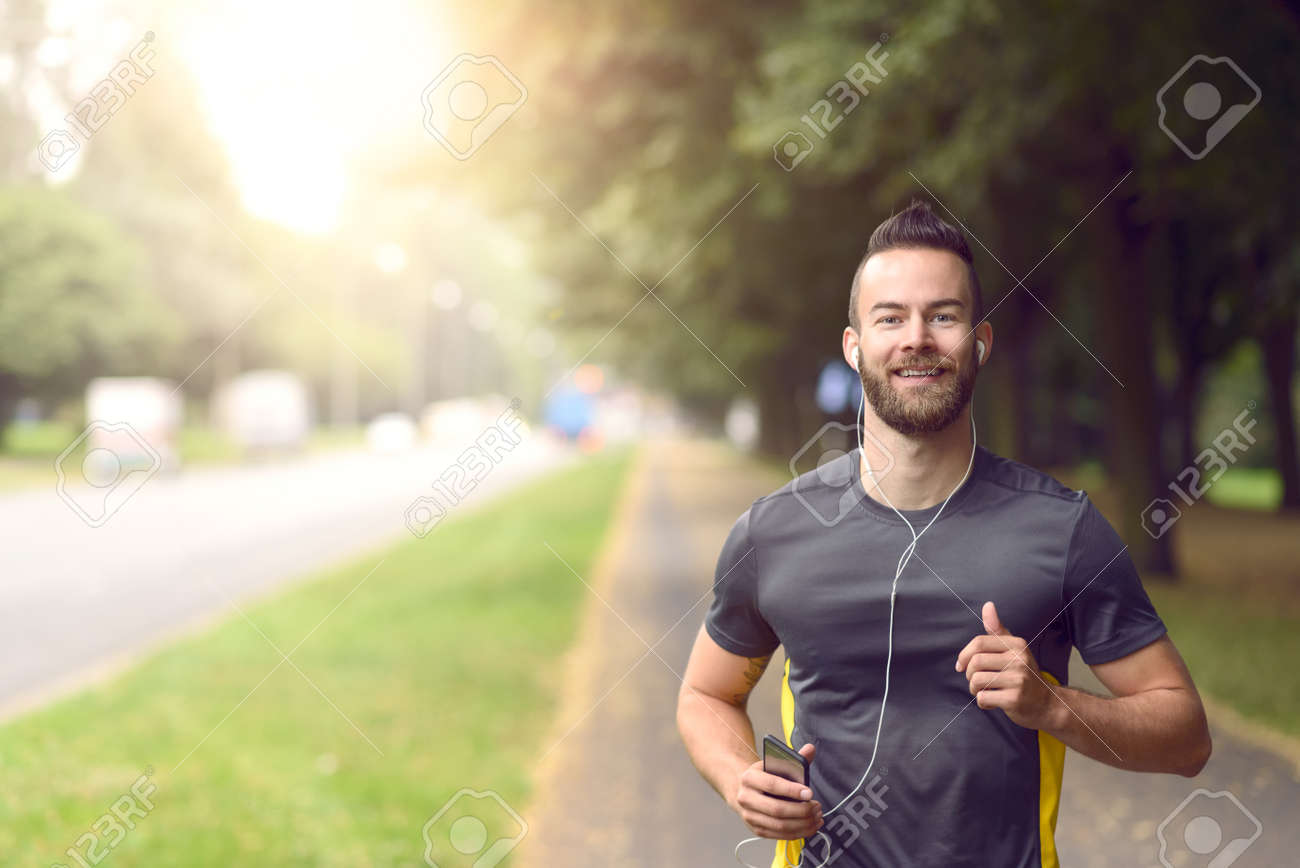 Man jogging along a tree lined sidewalk on a busy road approaching the camera in a fitness and active lifestyle concept - 61493150